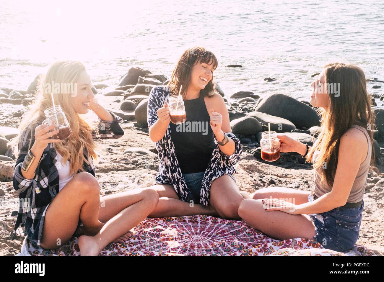Gruppe von Frauen Freunde sitzen und genießen die Freizeit Aktivität während der Sommerferien am Strand in der Nähe des Meeres. lächelt und fröhliche Menschen ha Stockbild
