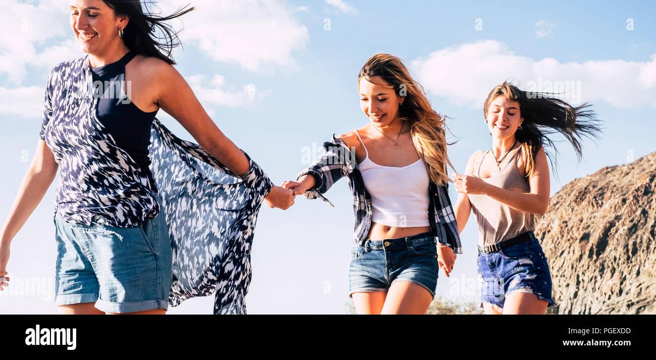 Drei fröhliche attraktive junge Frauen Freunde gehen gemeinsam die Hände mit blauem Himmel und Berg im Hintergrund. Freiheit und Glück genießen. Stockbild