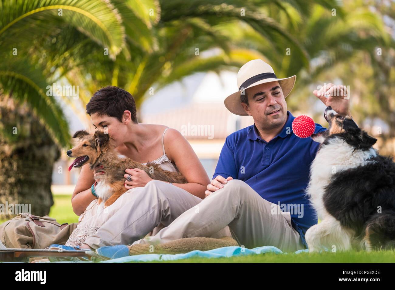 Schönes Mittelalter kaukasischen Paar sitzt auf dem Gras mit Palmen im Hintergrund beim Spielen mit zwei lustige und schöne Hunde und eine rote Kugel. Genießen Sie ein Stockbild