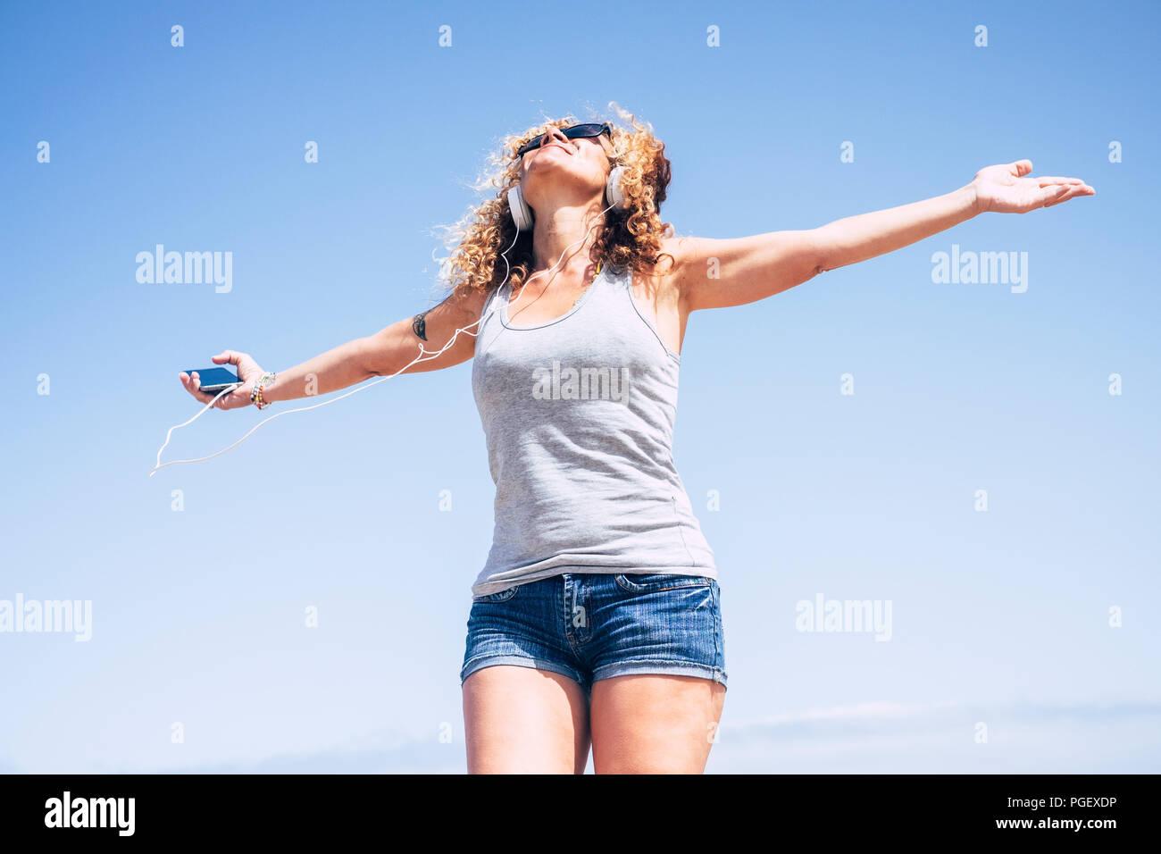 Gut gelaunt attraktiv Schön kaukasischen mittleren Alter lächelnde Frau am Strand in einem tropischen Ort, während die Musik, die mit der smart Telefon anhören. Menschen enjoyi Stockbild