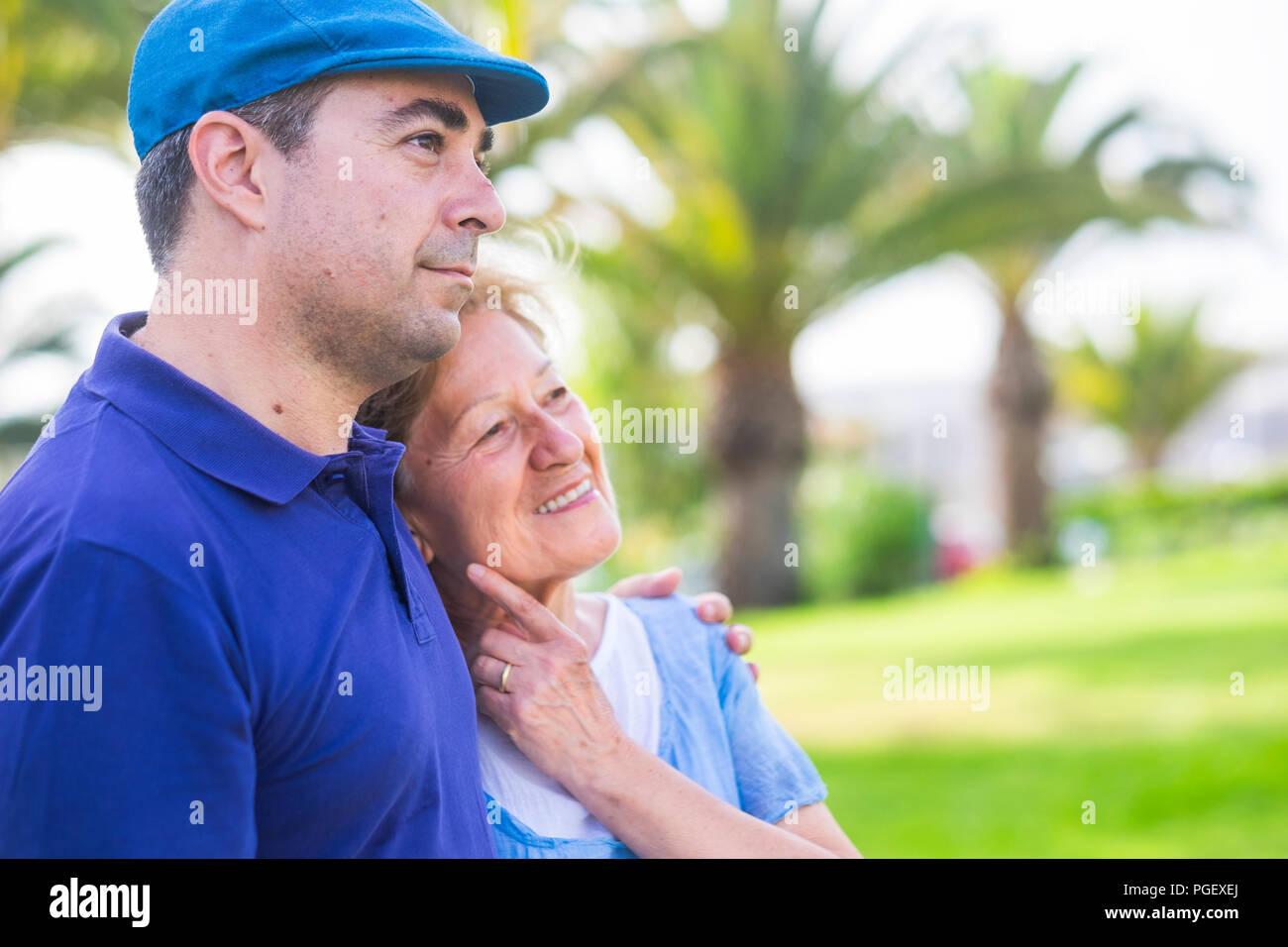 Unterschiedlichen Alters Paar wie Mutter und Sohn Aufenthalt umarmte zusammen in Outdoor Freizeitaktivitäten Aktivität mit Liebe und Emotionen. den Tag im Park genießen mit Gree Stockbild