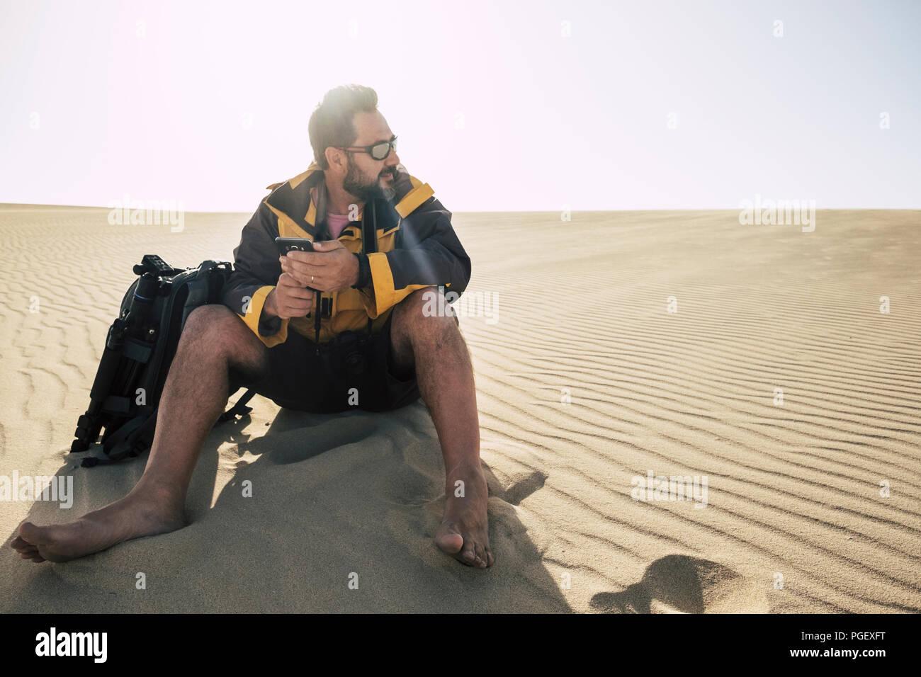 Lonely kaukasischen mittleren Alter Mann reisen Barfuß im desrt mit Rucksack und Telefon und Stativ Bilder zu machen. alternative Reisen Urlaub Begriff Stockbild