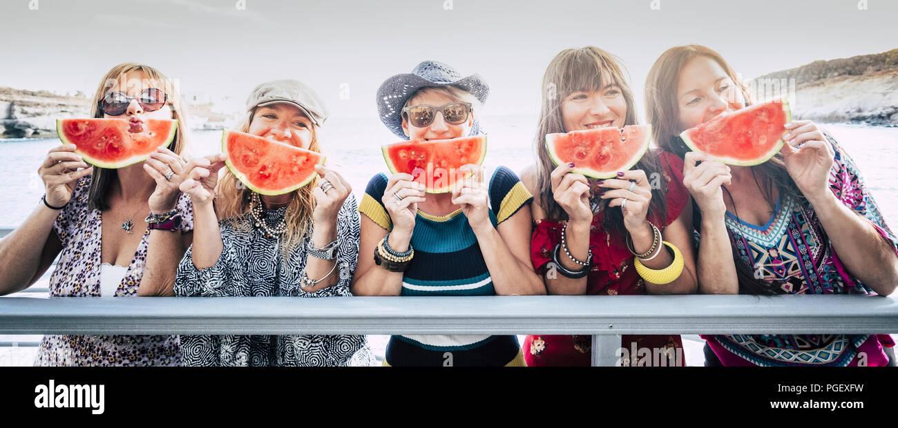 Aufenthalt Gruppe von Nizza cute fröhlicher junger Frauen Freunde zusammen Spaß und Freundschaft unter einem roten Wassermelone in der Nähe des Gesichts. Stockbild