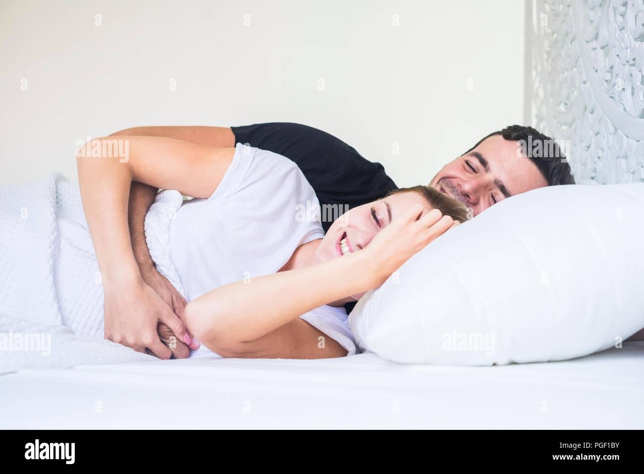 Glückliches junges Paar hinlegen und schlafen oder aufwachen in den frühen Morgen zu Hause. Weiß Schlafzimmer zu Hause und die Menschen umarmen mit Liebe und relationshi Stockbild