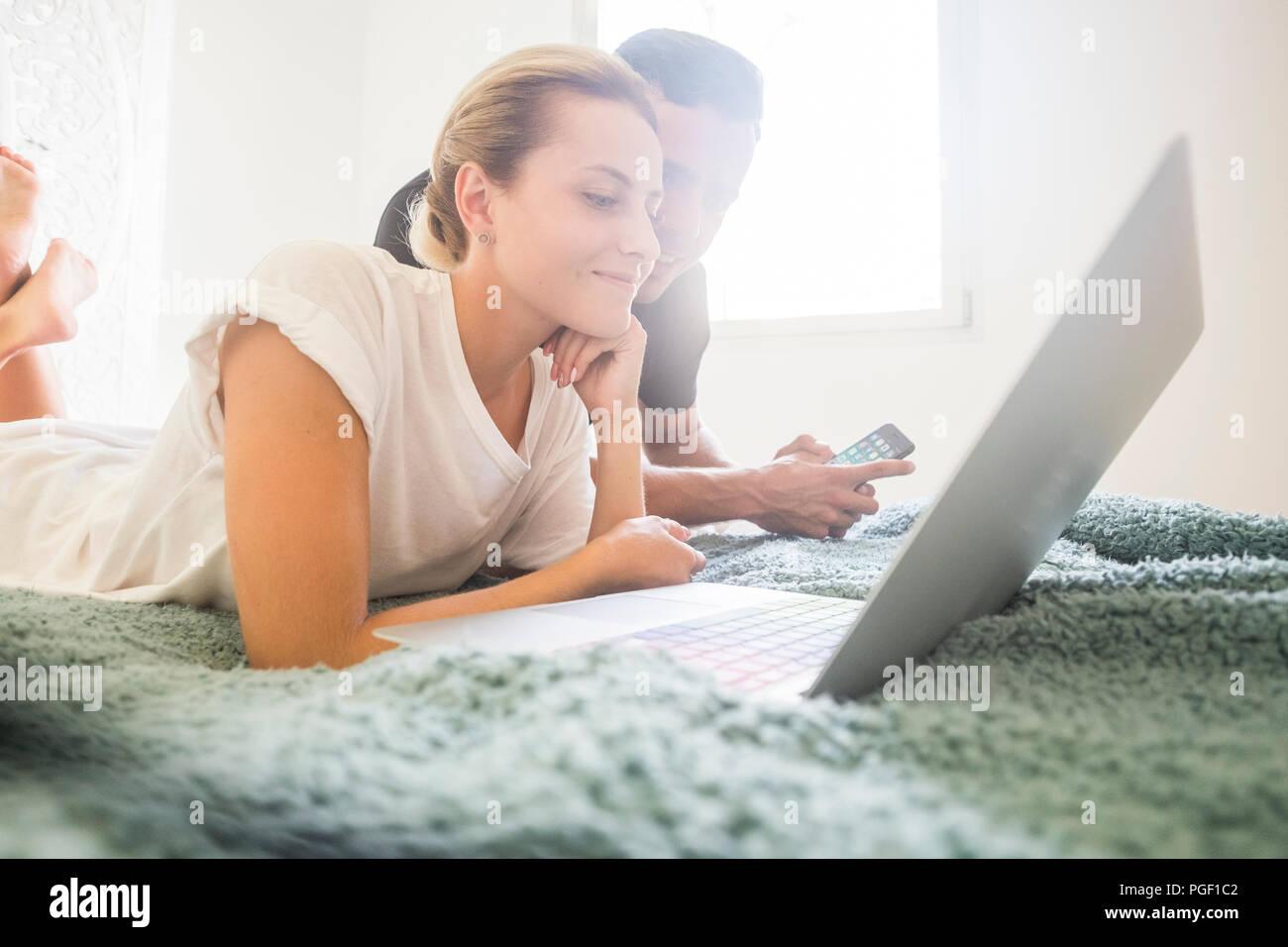 Schön kaukasischen jungen attraktiven Paar Aufenthalt legte sich auf das Bett arbeiten mit Laptop und Handy Internet verbunden. indoor home freizeit Aktivität Stockbild