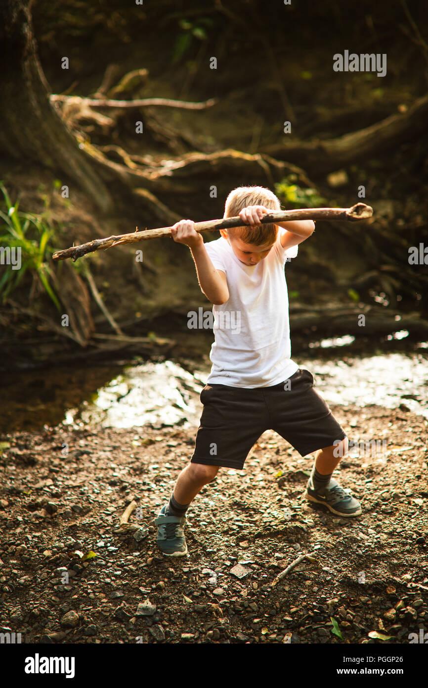 Jungen spielen kämpfen mit Stick in Wäldern. Stockbild