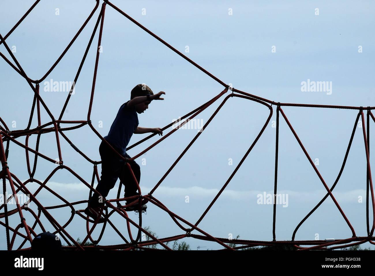 Klettergerüst Mit Seilen : Silhouette der junge auf seil hohe klettergerüst dem spielplatz