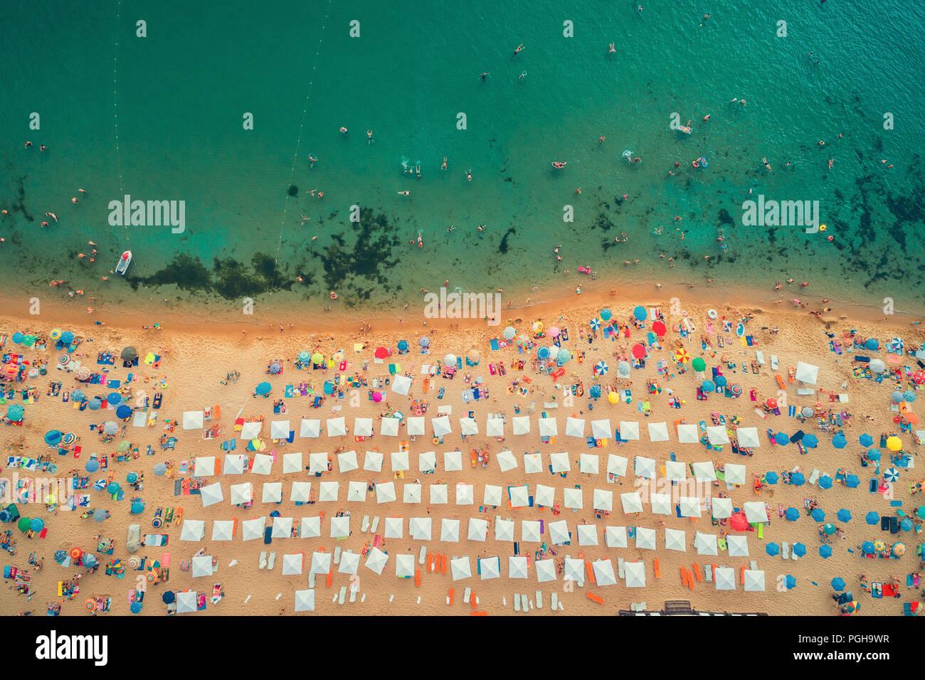 Antenne top Aussicht auf den Strand. Menschen, Schirme, Sand und Meer Wellen Stockfoto