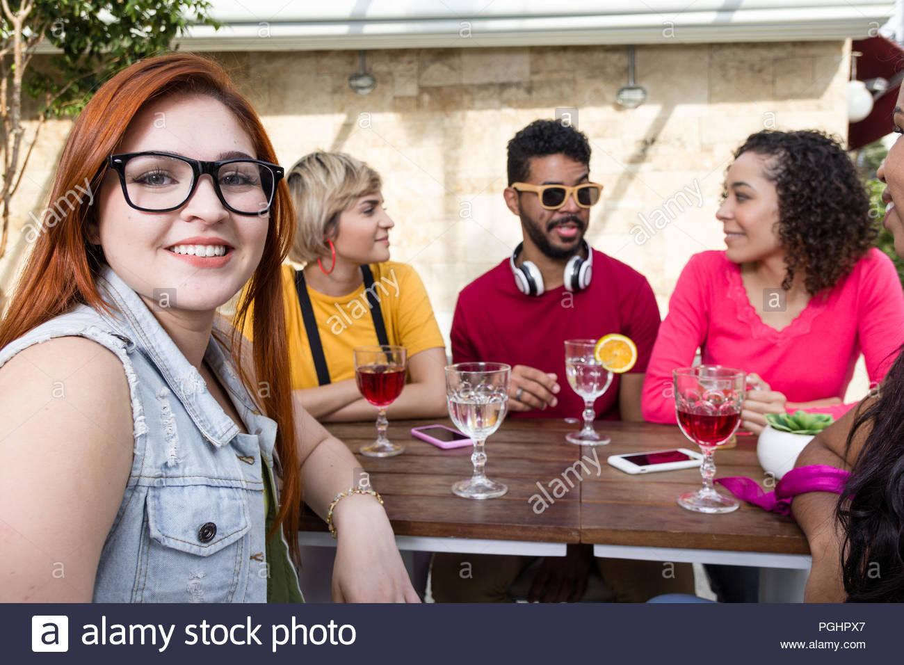 Happy millennials Freunde jubeln und zusammen trinken im Cafe Bar im Freien. Mixed Race Gruppe von Freunden Spaß an Restaurant außerhalb haben. Feder, wa Stockbild