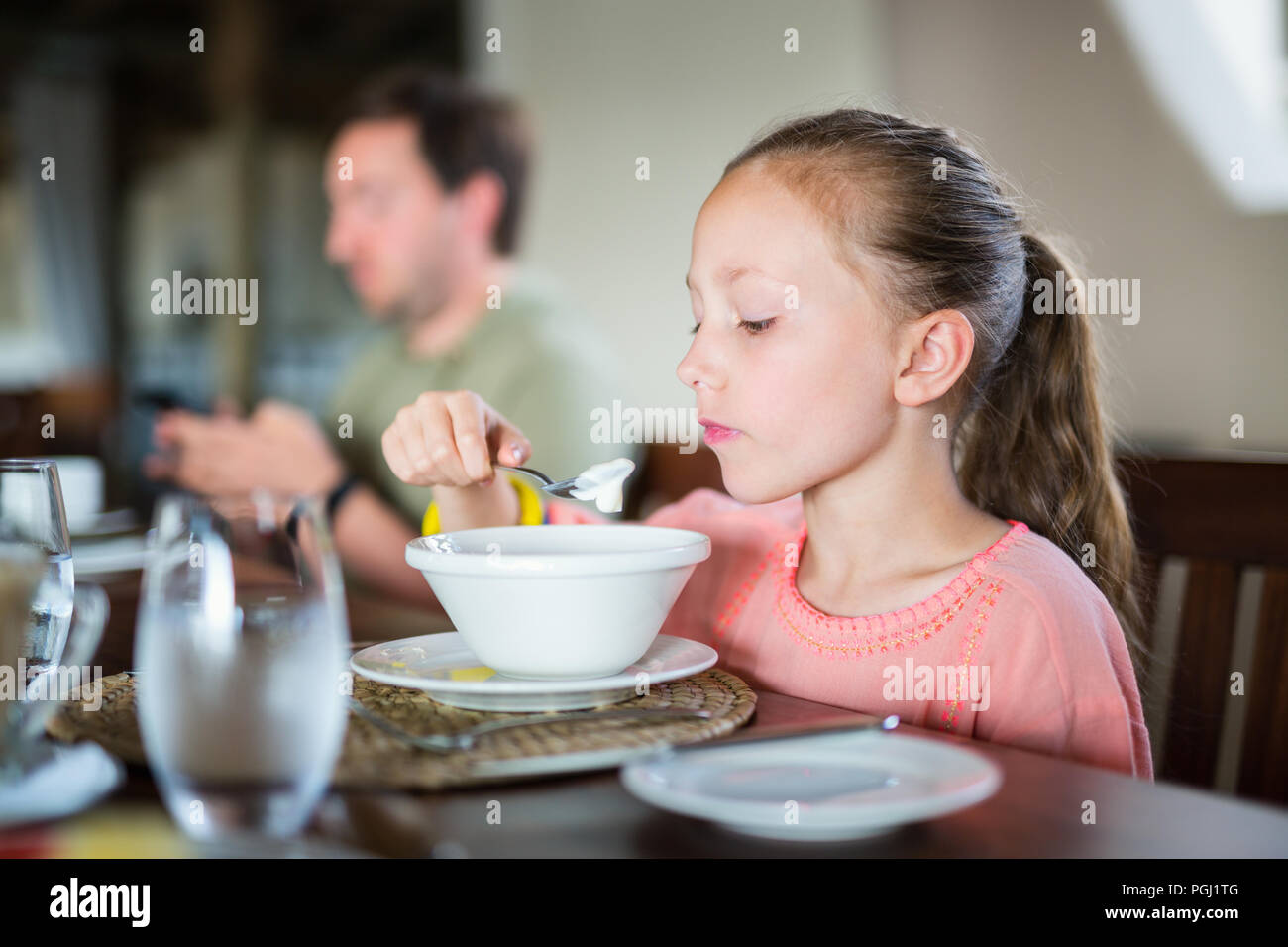 Adorable kleine Mädchen essen Frühstück zu Hause oder im Restaurant Stockbild