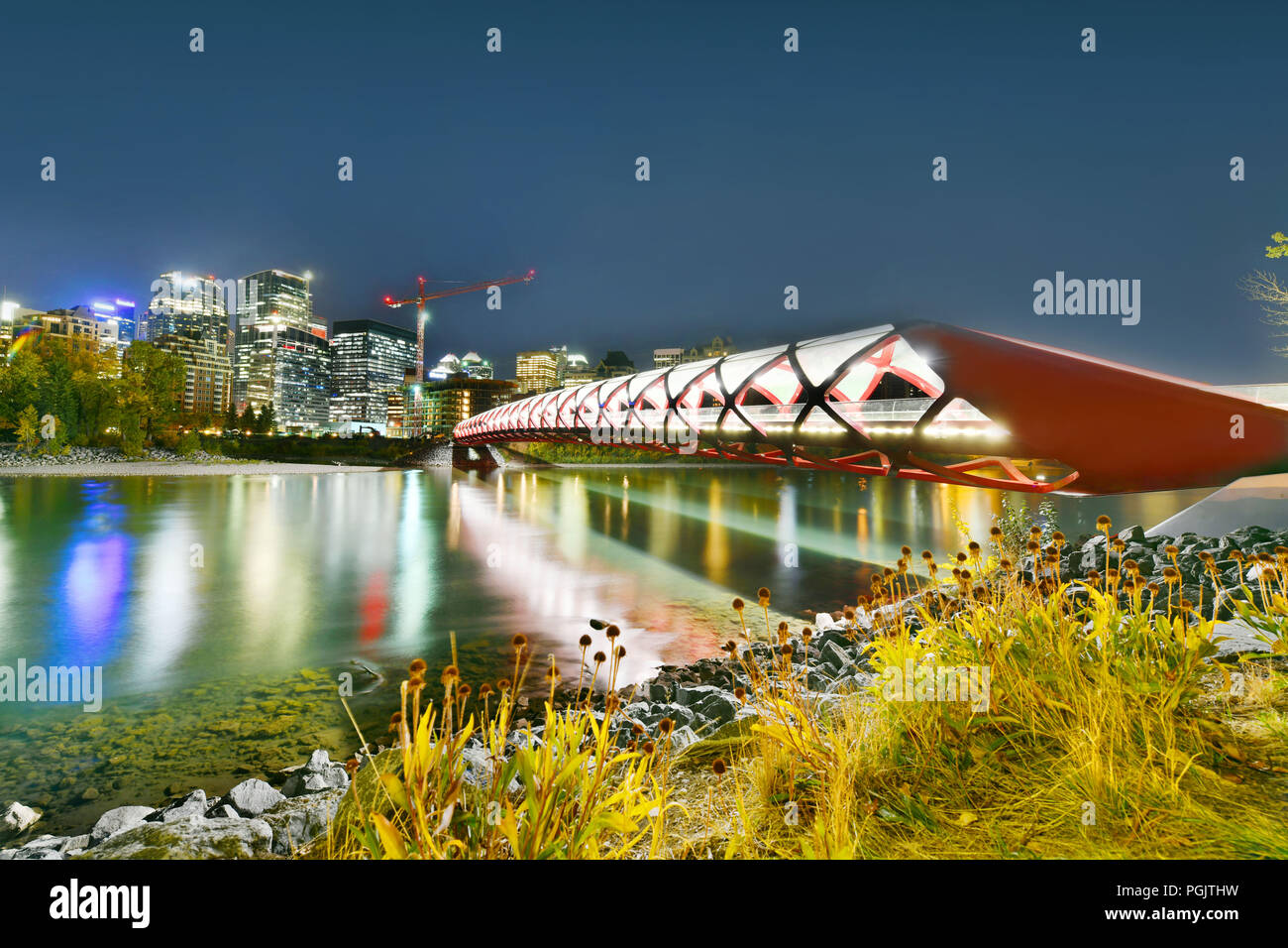 Peace Bridge mit Bow River und ein Teil der Downtown Calgary in Alberta, Kanada in der Nacht Stockbild