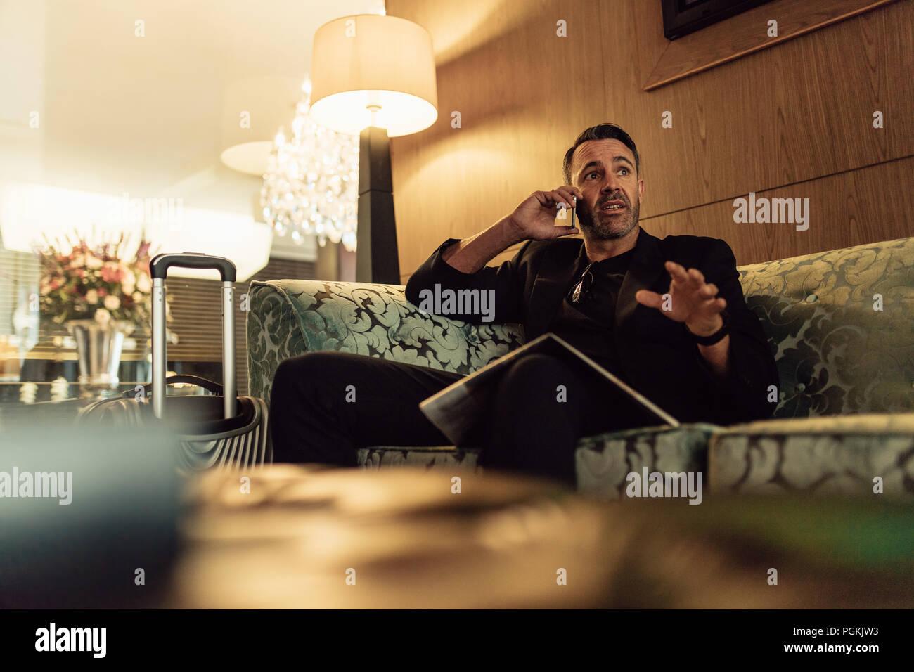 Reifen Geschäftsmann in der Lobby sitzen und Gespräch am Handy. Geschäftsmann auf wartet im Hotel Foyer, Anruf. Stockbild