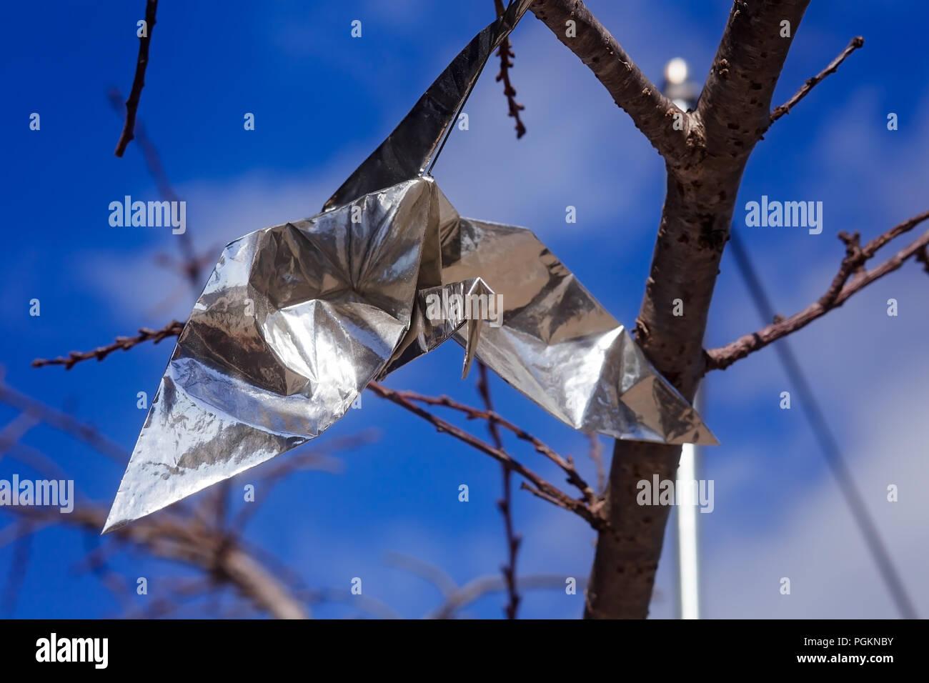 Silberfolie Origami Papier Kran, hängend an einer Kirsche Blüte Baum, in San Francisco Japantown Stockbild