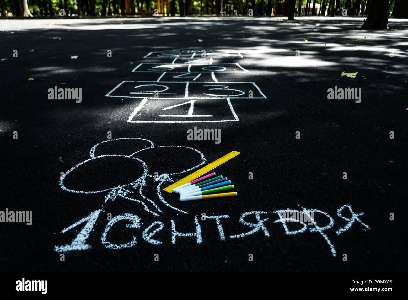 Weißer Kreide auf den schwarzen Asphalt Gedenkstein in russisch September 1. Gelbe Linie, farbige Markierungen, bemalt Kugeln, Hopse Stockbild