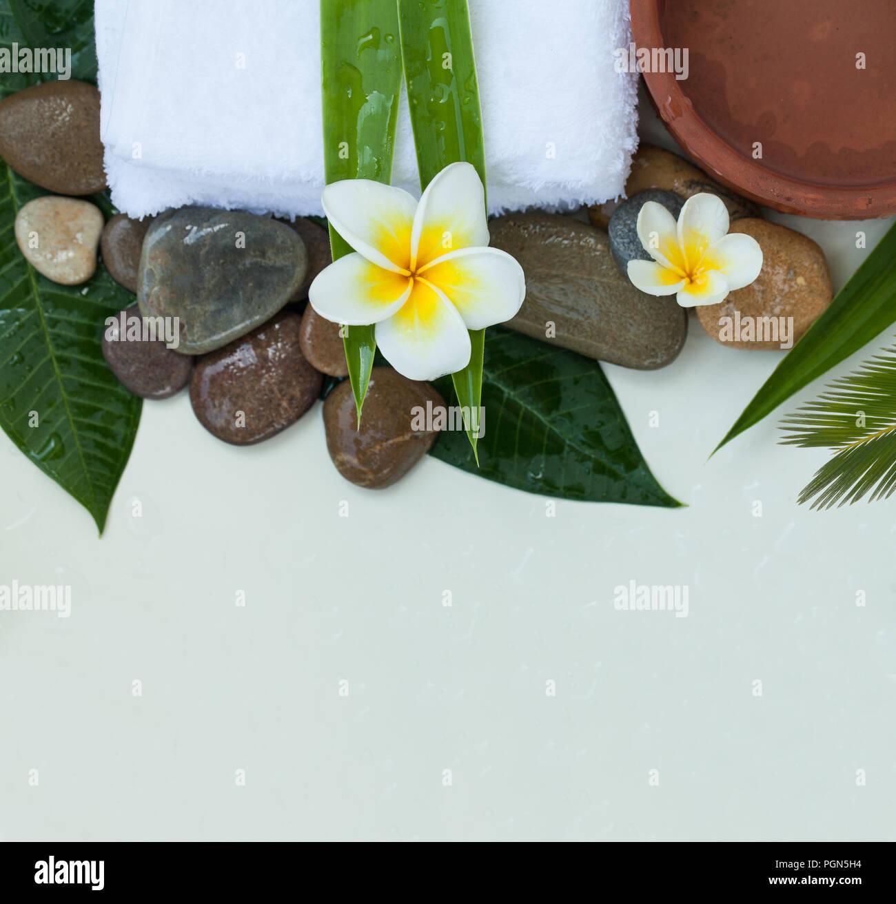 Spa, Wellness oder Einstellung mit tropischen Blumen, Schüssel mit Wasser, Handtuch und dunklen Steinen Stockbild