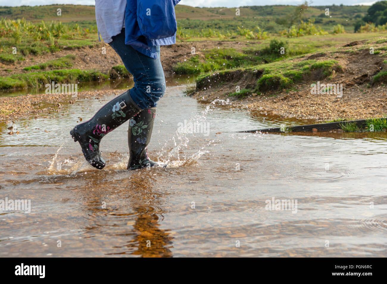 watch 02414 b4db1 Frau mit schwarzen Blumen Gummistiefel laufen durch Wasser ...