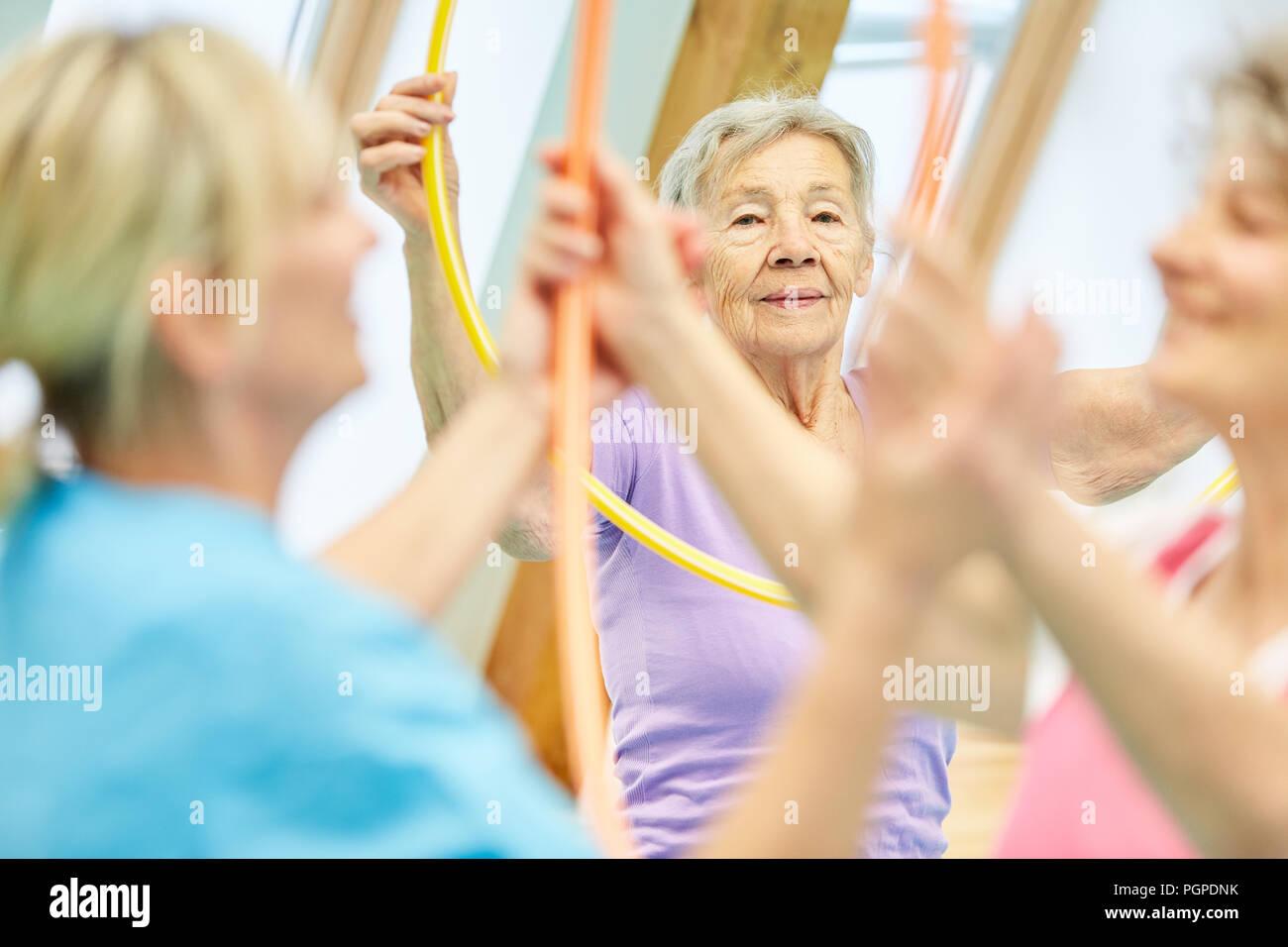 Senioren werden von Physiotherapeuten bei Übungen mit dem Reifen Stockbild