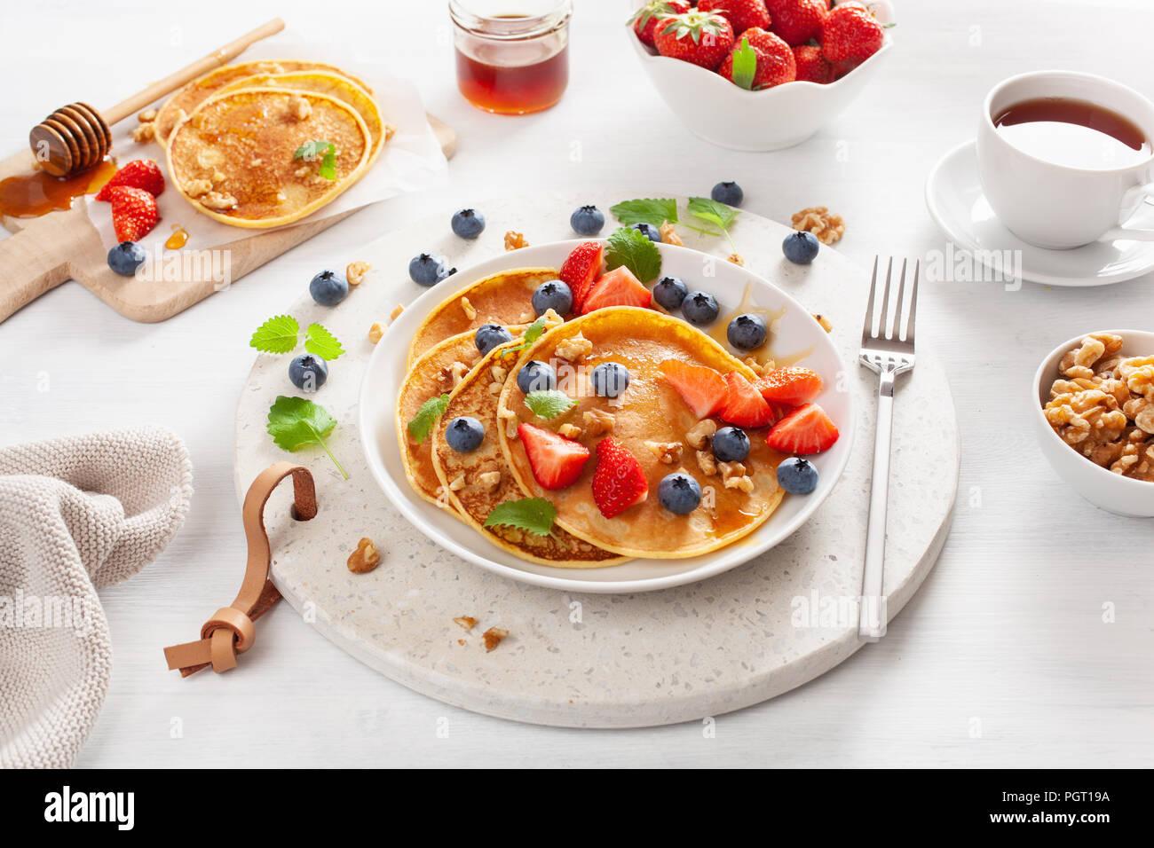 Pfannkuchen mit Heidelbeeren Erdbeere Honig und Nüssen für Frühstück Stockbild