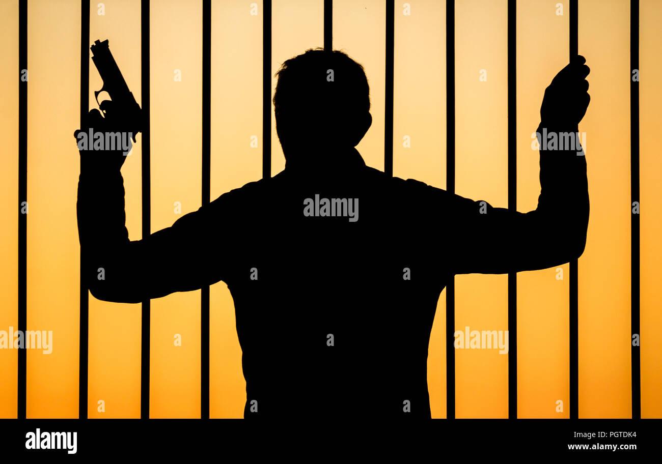 Silhouette der Mann mit Pistole Schauen durch Bars: Konzept Bild für Pistole Kriminalität, illegale Waffen / Waffen, Bandenkriminalität, Waffen im Gefängnis... Stockbild