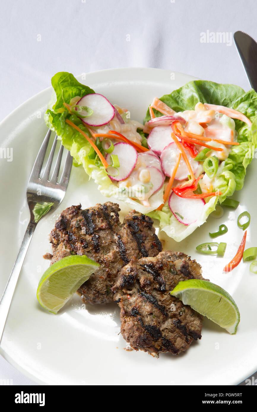 Spicy Chili und Kalk Lamm Burger mit Mais und Rettich Salat. Stockbild