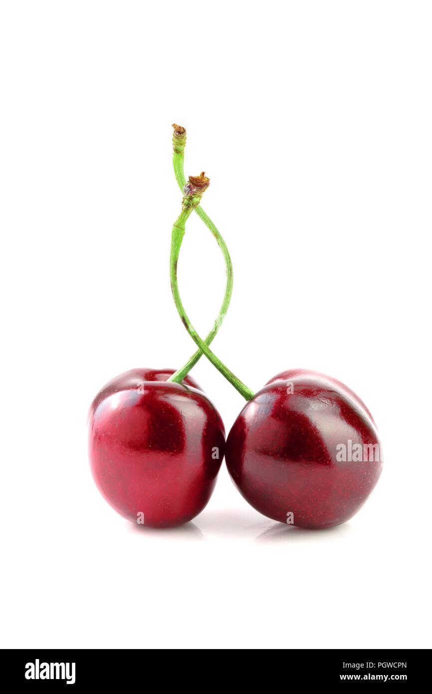 Süße rote Kirschen auf weißem Hintergrund Makro isoliert. Stockfoto