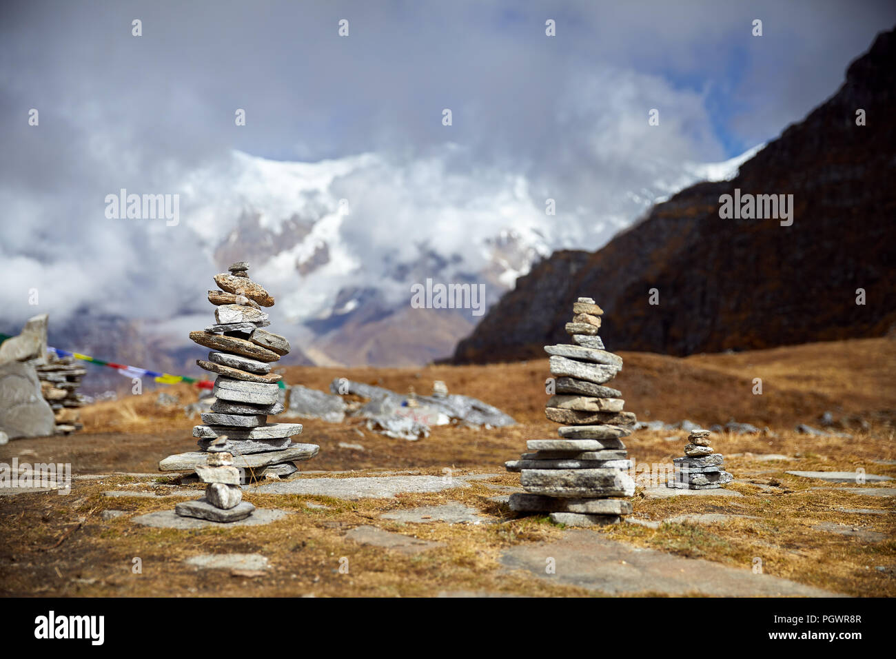 Kleine Haufen von Steinen am Mardi Himal Trek und bewölkt Gipfeln des Himalaya in Nepal Stockfoto