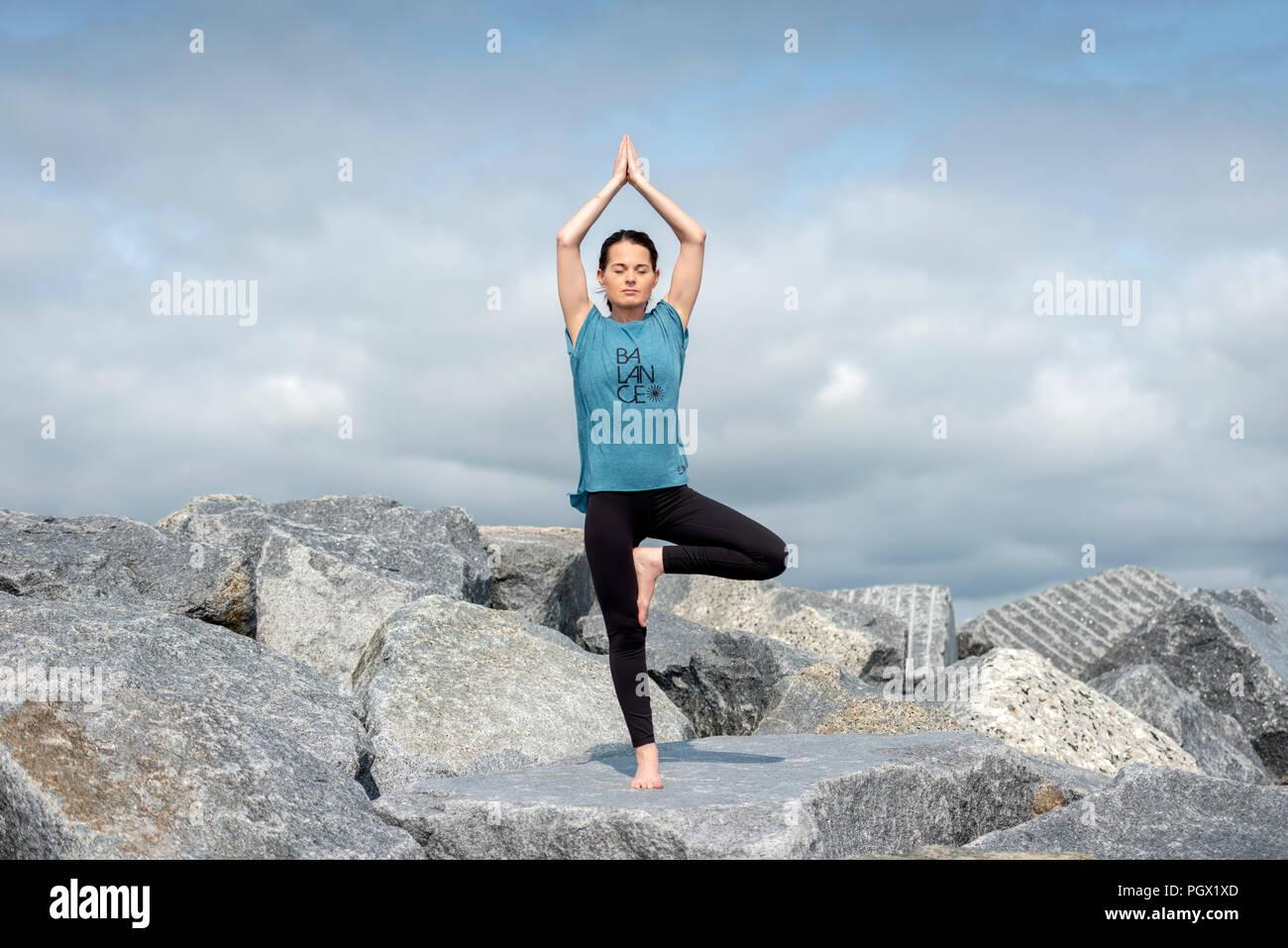 "Frau, Yoga, Baum darstellen, trägt ein T-Shirt mit ""Balance""-Slogan. Stockbild"