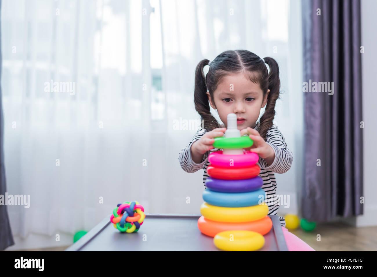 Kleine Mädchen spielen kleines Spielzeug Bänder in Home