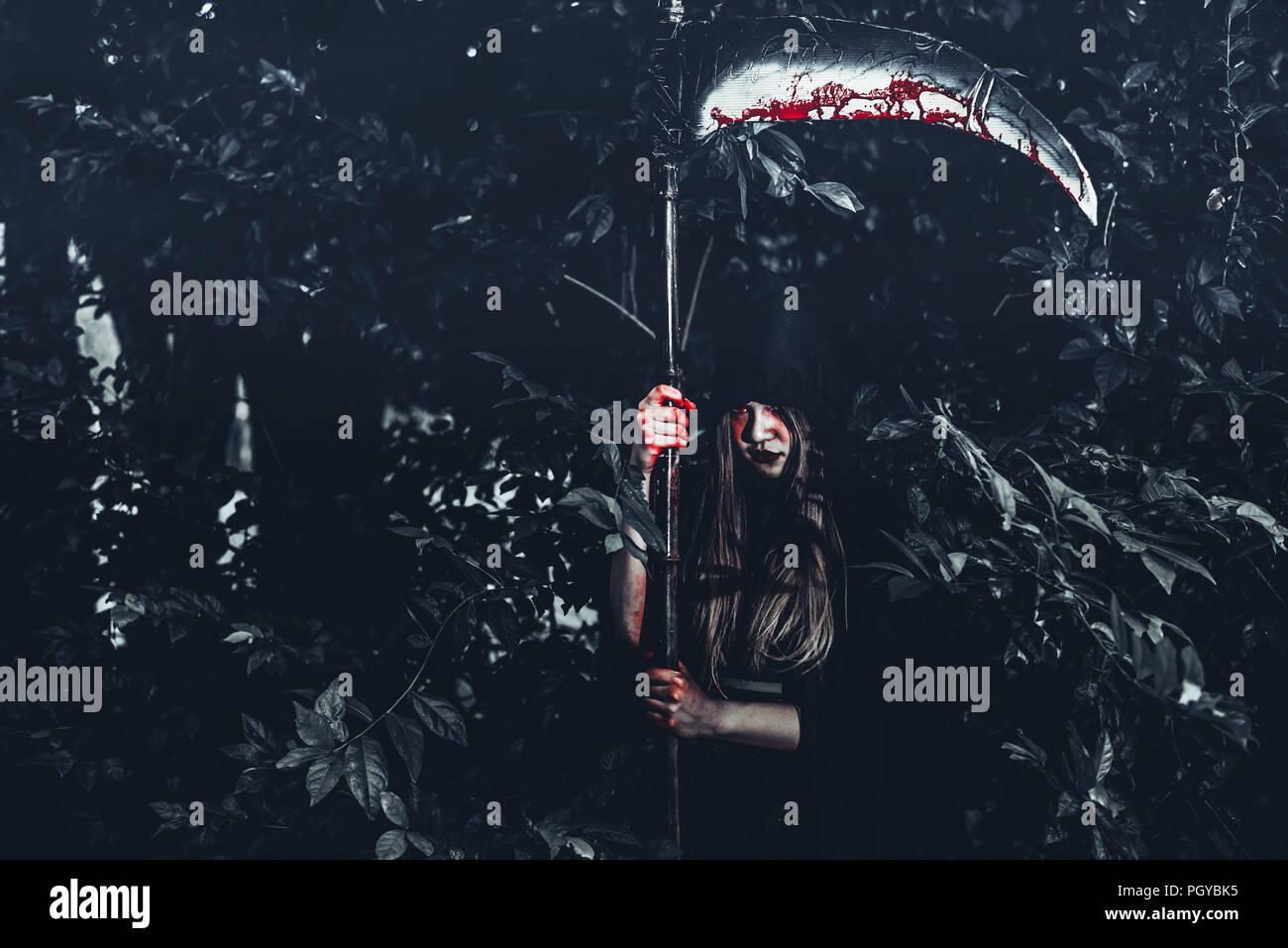 Weiblicher Dämon Hexe mit Bloody reaper stand vor der Geheimnis Wald Hintergrund. Halloween und religiöses Konzept. Daemon Engel und Satan Thema. Stockfoto