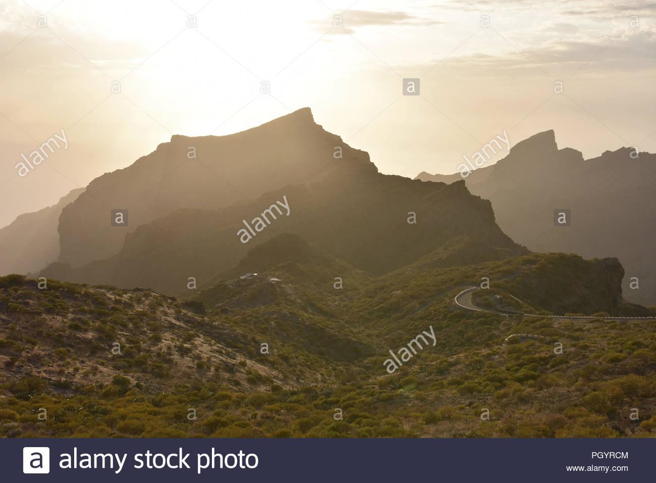 Den Berg Macizo de Teno - Sonne hinter vulkanischen Gipfeln der Teno-gebirge im Nordwesten von Teneriffa Kanarische Inseln Spanien. Stockbild