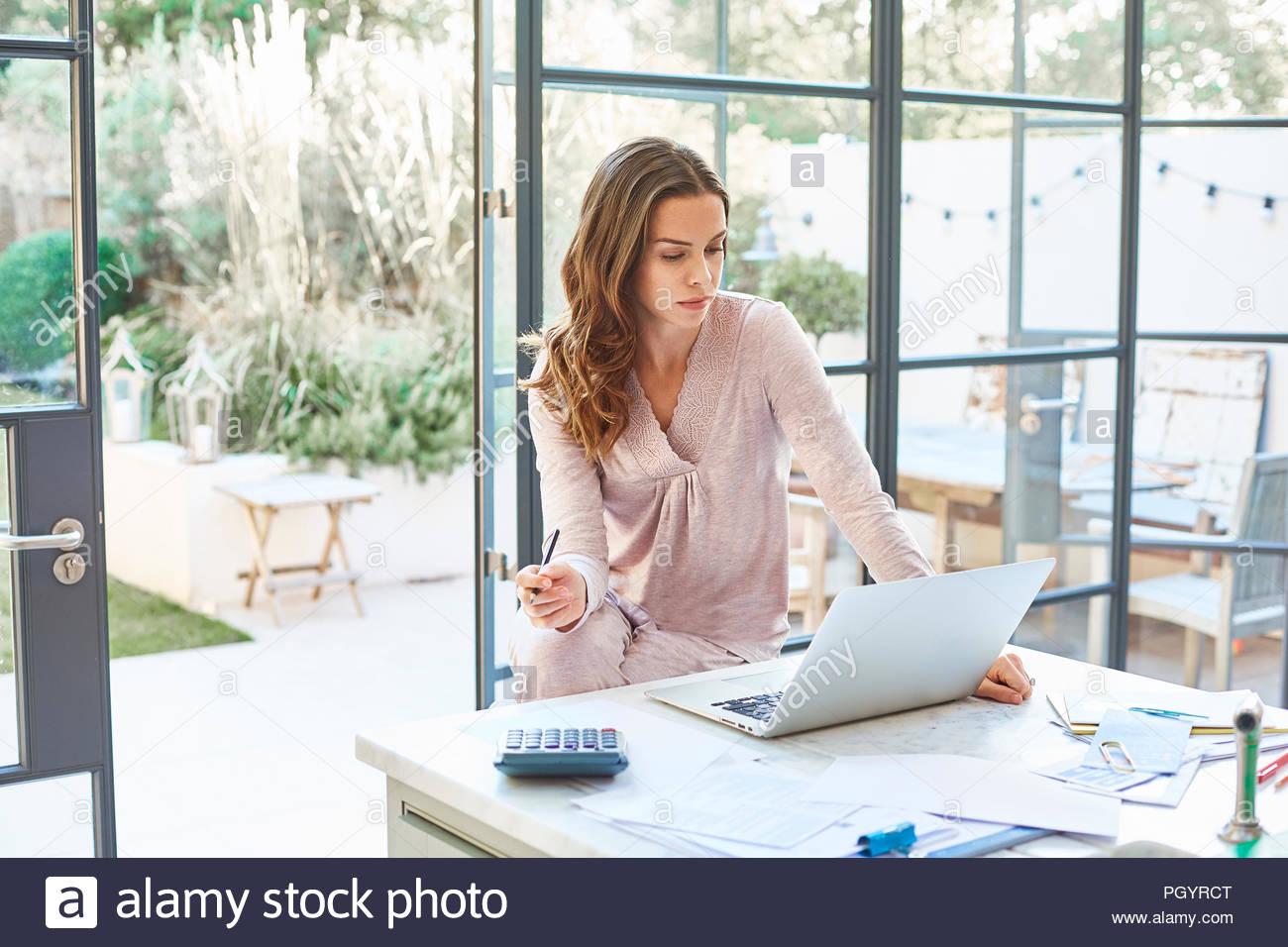 Mitte Erwachsene Frau mit Laptop am Küchentisch. Stockfoto