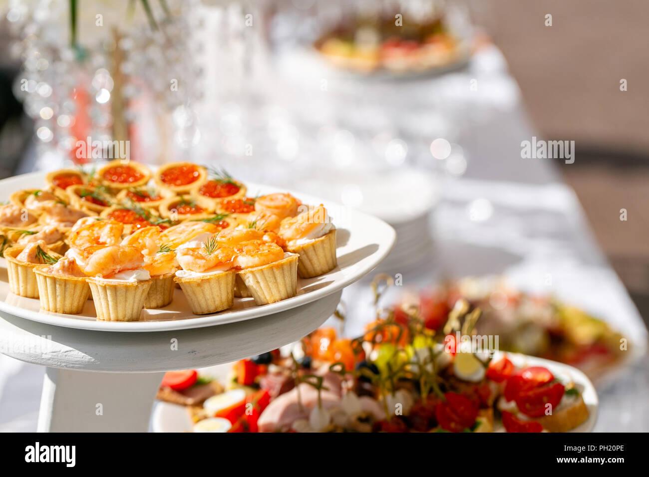 Feierliches Bankett. Viele Gläser Champagner oder Wein auf dem Tisch im Restaurant Buffet mit vielen leckeren Snacks. Canapees, Bruschetta, und kleine Desserts auf Holzplatte board Stockbild