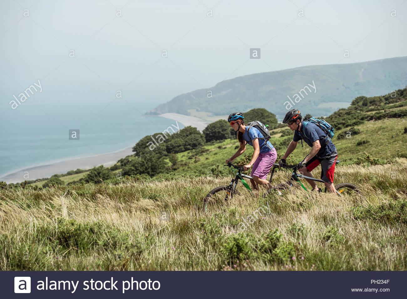 Paar Mountainbiken auf Hügel in Porlock Wehr, England Stockfoto