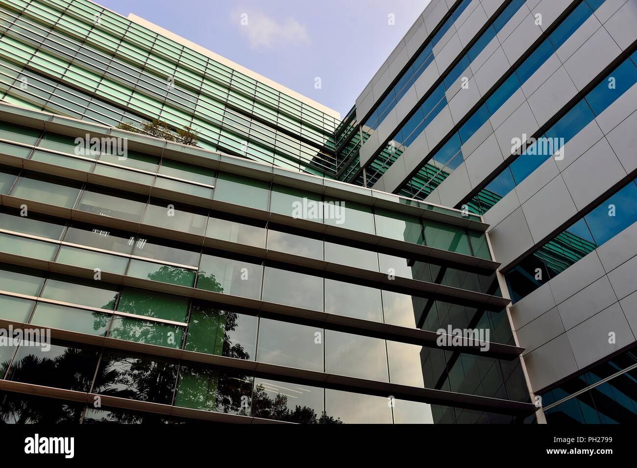 Abstrakte Glasfassade der modernen Bürogebäude in der Innenstadt von Singapur mit symmetrischen Mustern, Reflexionen und Perspektive als abstrakt Hintergrund Stockfoto