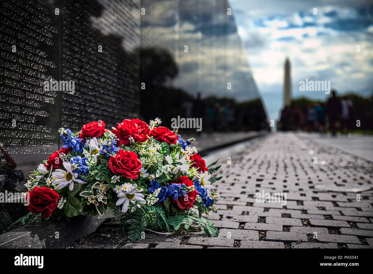 Blumen gegen den Vietnam Veterans Memorial in Washington, DC. Stockbild