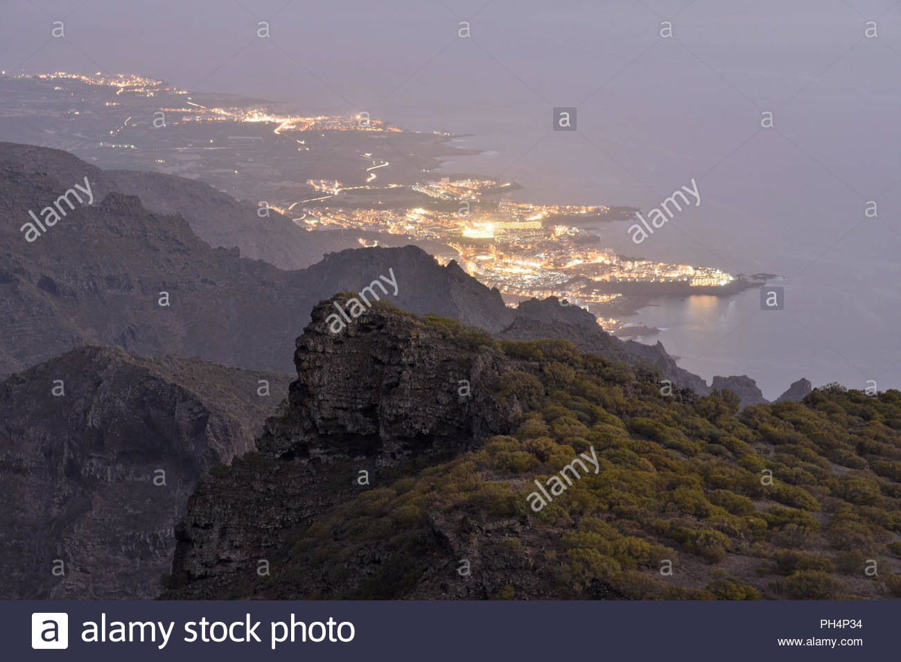 Städte von Los Gigantes und Puerto de Santiago leuchten in der Abenddämmerung. Erhöhte Ansicht vom Teno-gebirge im Nordwesten von Teneriffa Kanarische Inseln Spanien. Stockbild