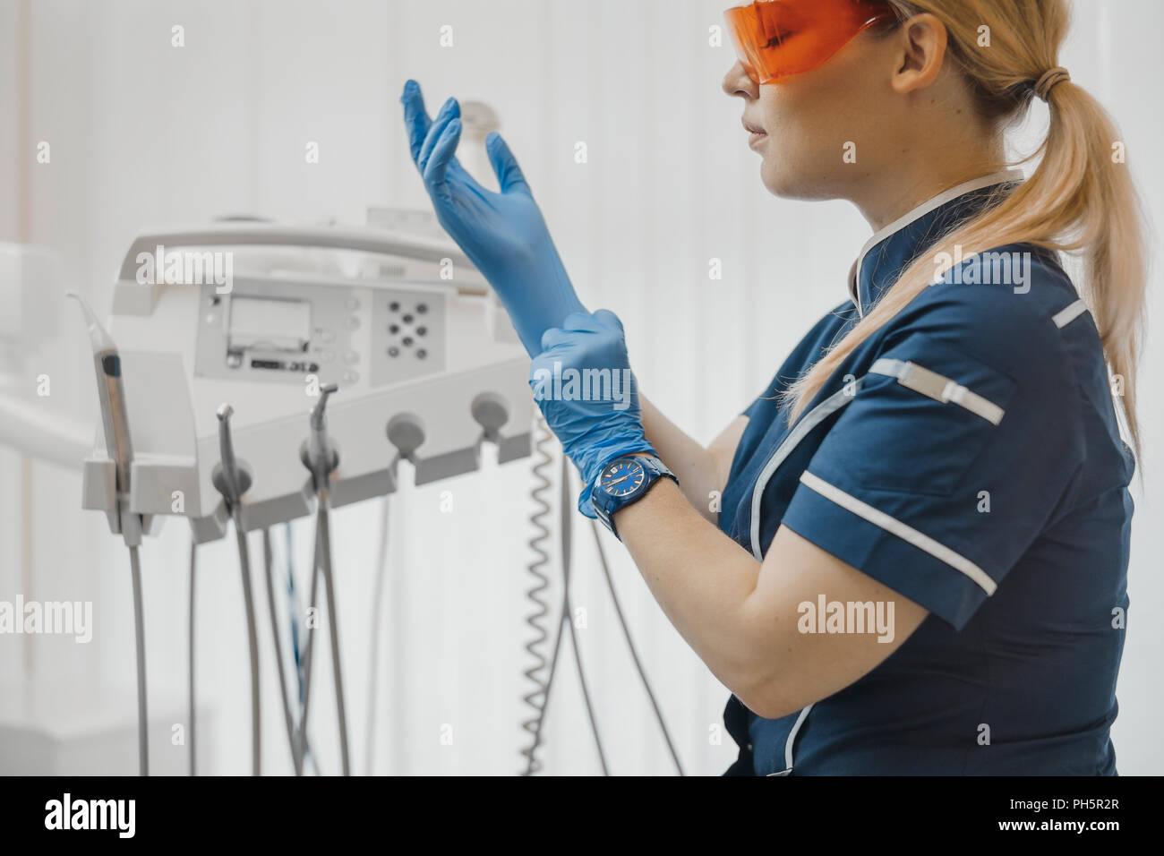 Nahaufnahme von Zahnarzt sitzt neben zahnmedizinischen Ausrüstung und setzen auf Handschuhe. Stockbild