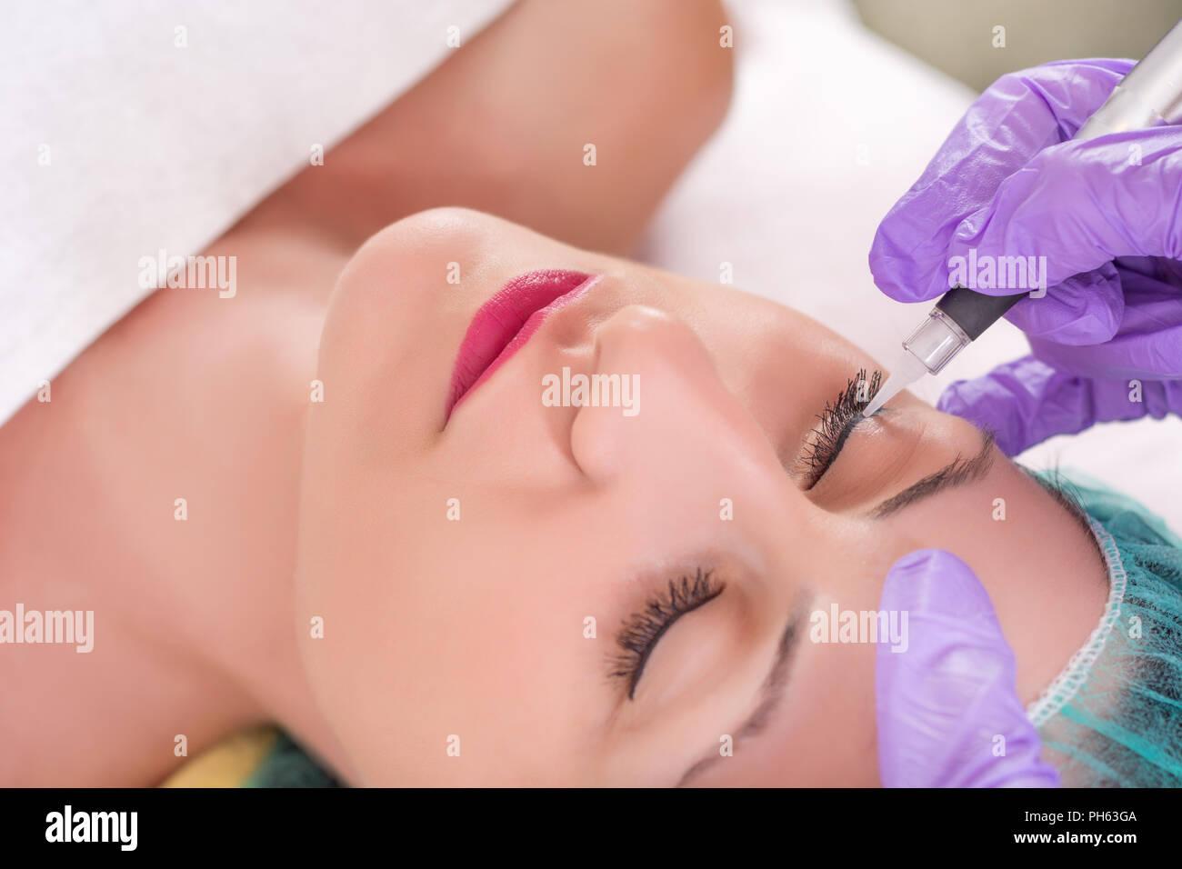 Kosmetiker Anwendung von Permanent Make-up von Augen auf schönes Mädchen in Beauty Studio. Eyeliner Tattoo mit professionellem Werkzeug Stockbild