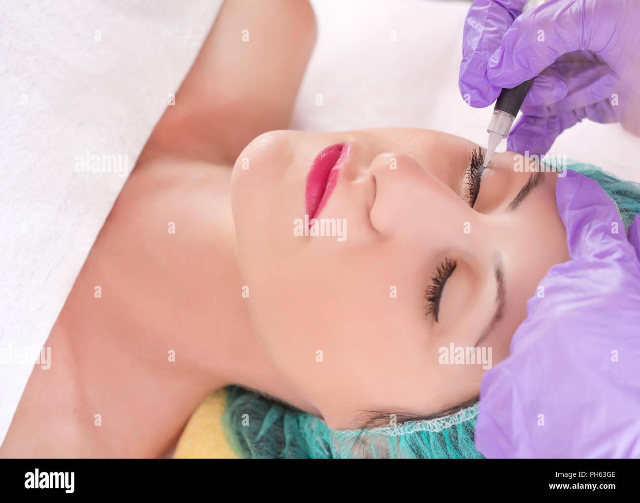 Kosmetiker Permanent Make up Eyeliner auf Schöne junge Mädchen in Beauty Studio. Tätowierer, eyeliner mit Werkzeug und Schutzhandschuh Stockbild