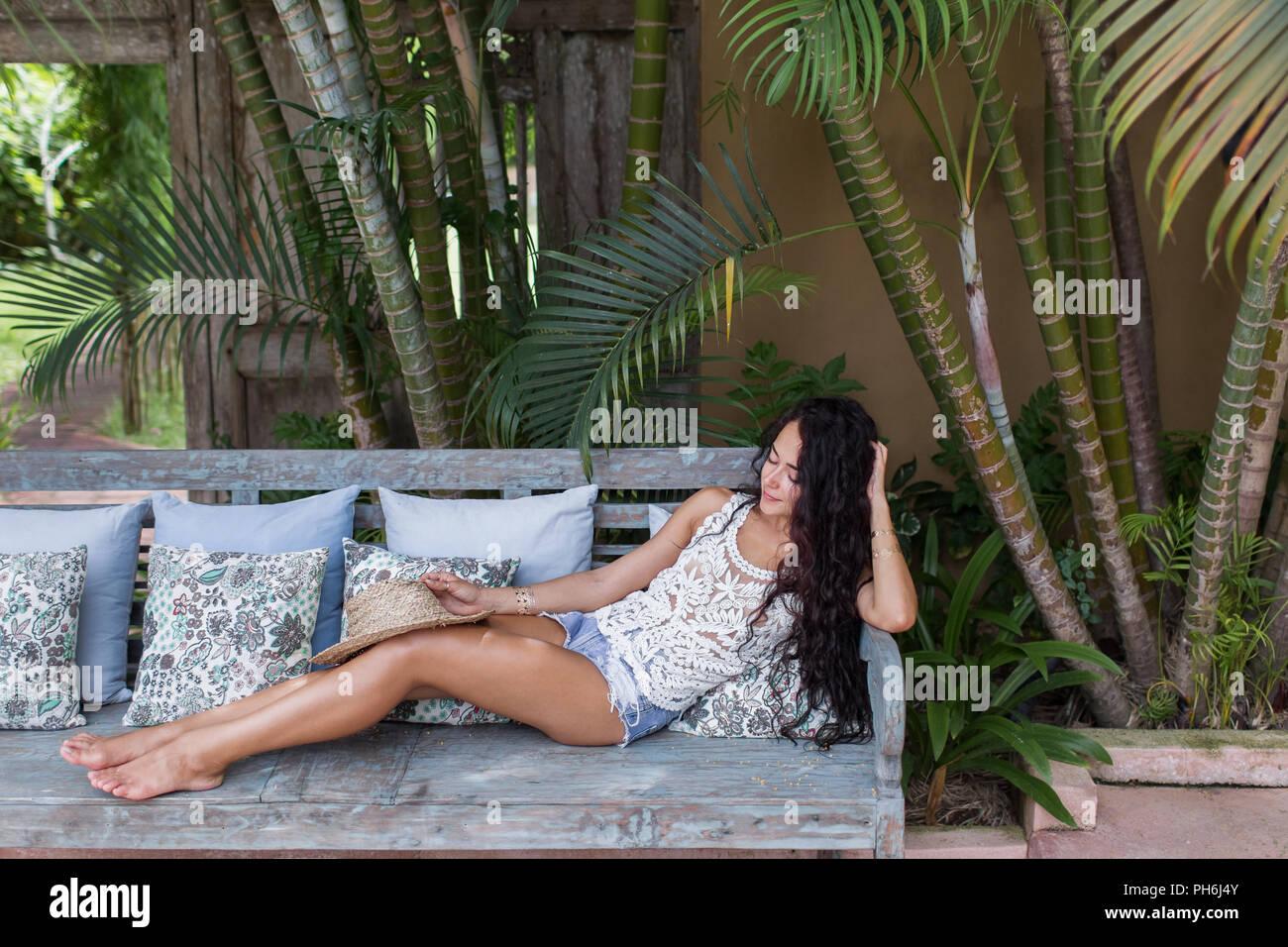 Schöne junge Frau mit langen schwarzen Haaren entspannt auf einem Sofa mit Strohhut Stockbild
