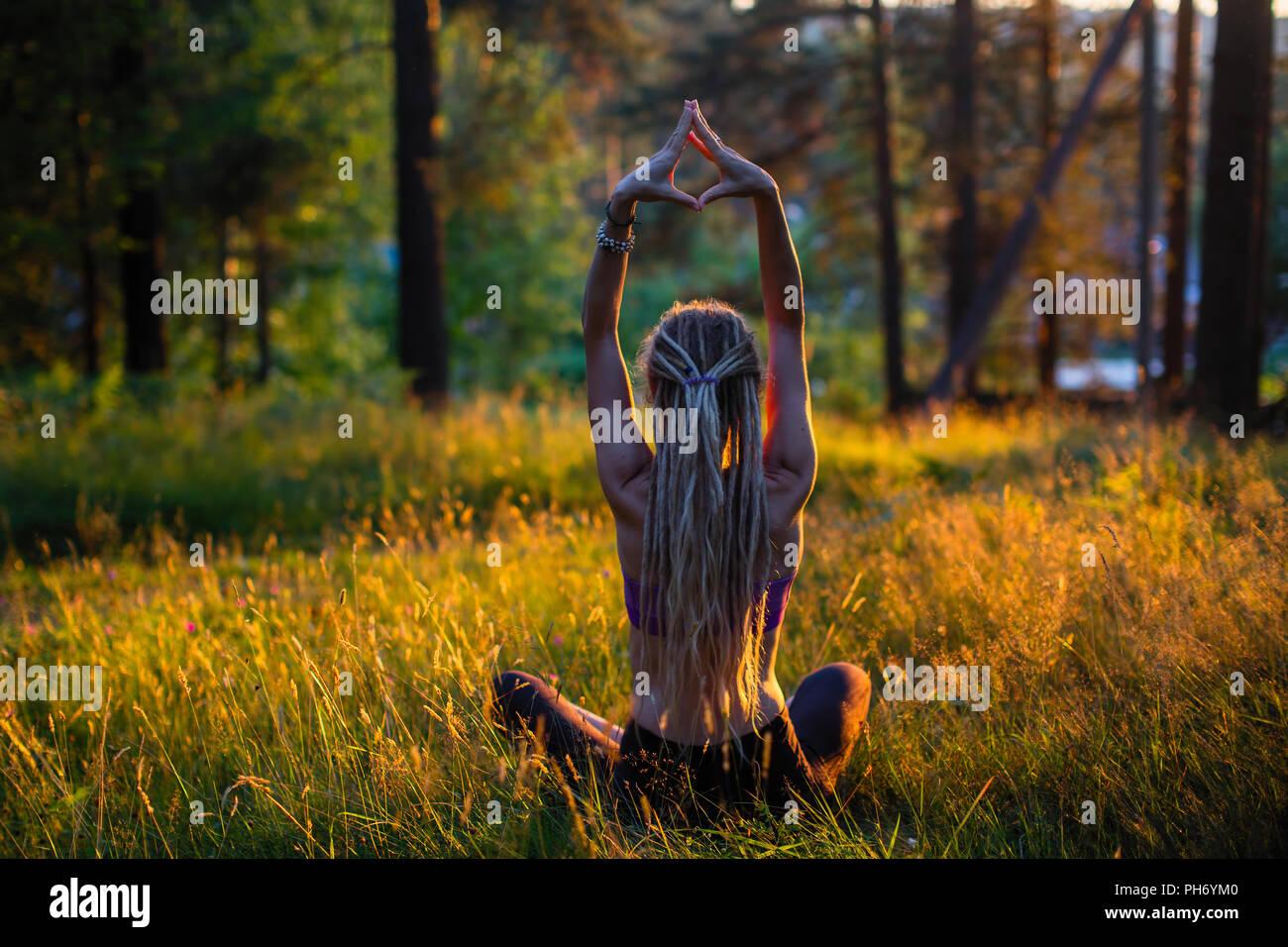 Yoga Frau auf einem malerischen Waldwiese in einem grünen Wald. Stockbild