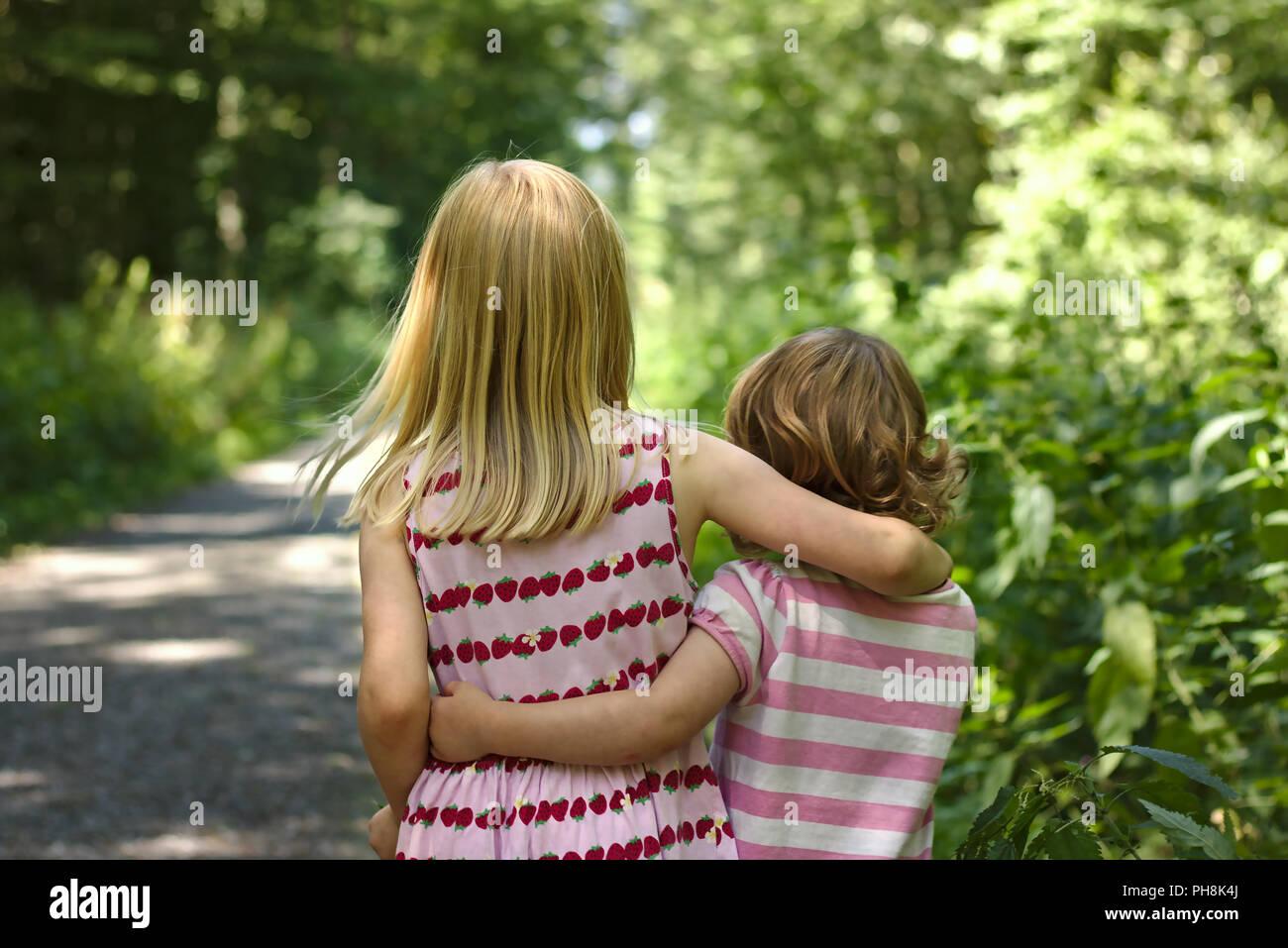 Zwei kleine Mädchen, Sommer Kleider gehen Arm in Arm entlang Sonniger Wald Trail Stockbild