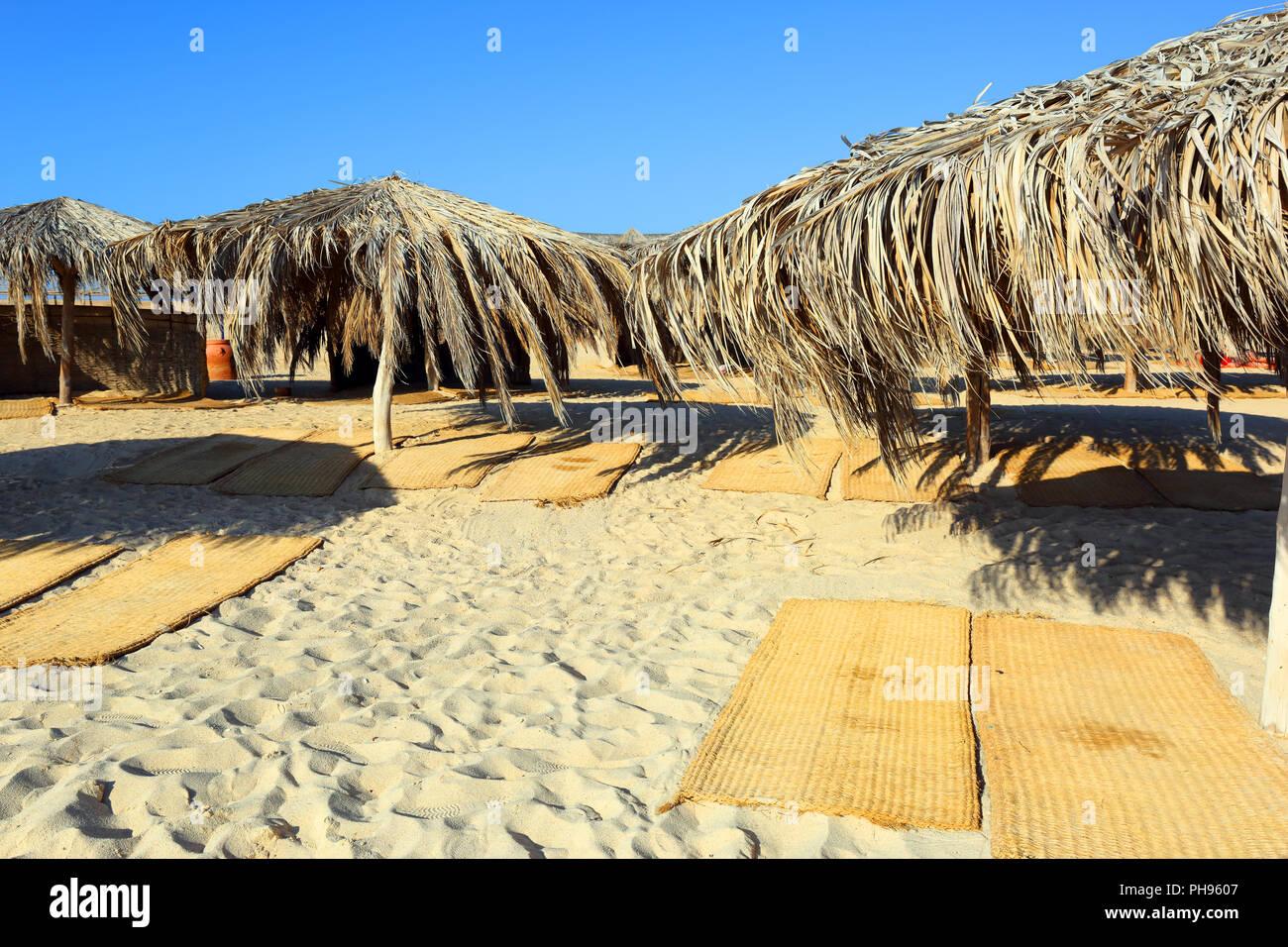 Schirme und Auflagen am Strand Stockbild