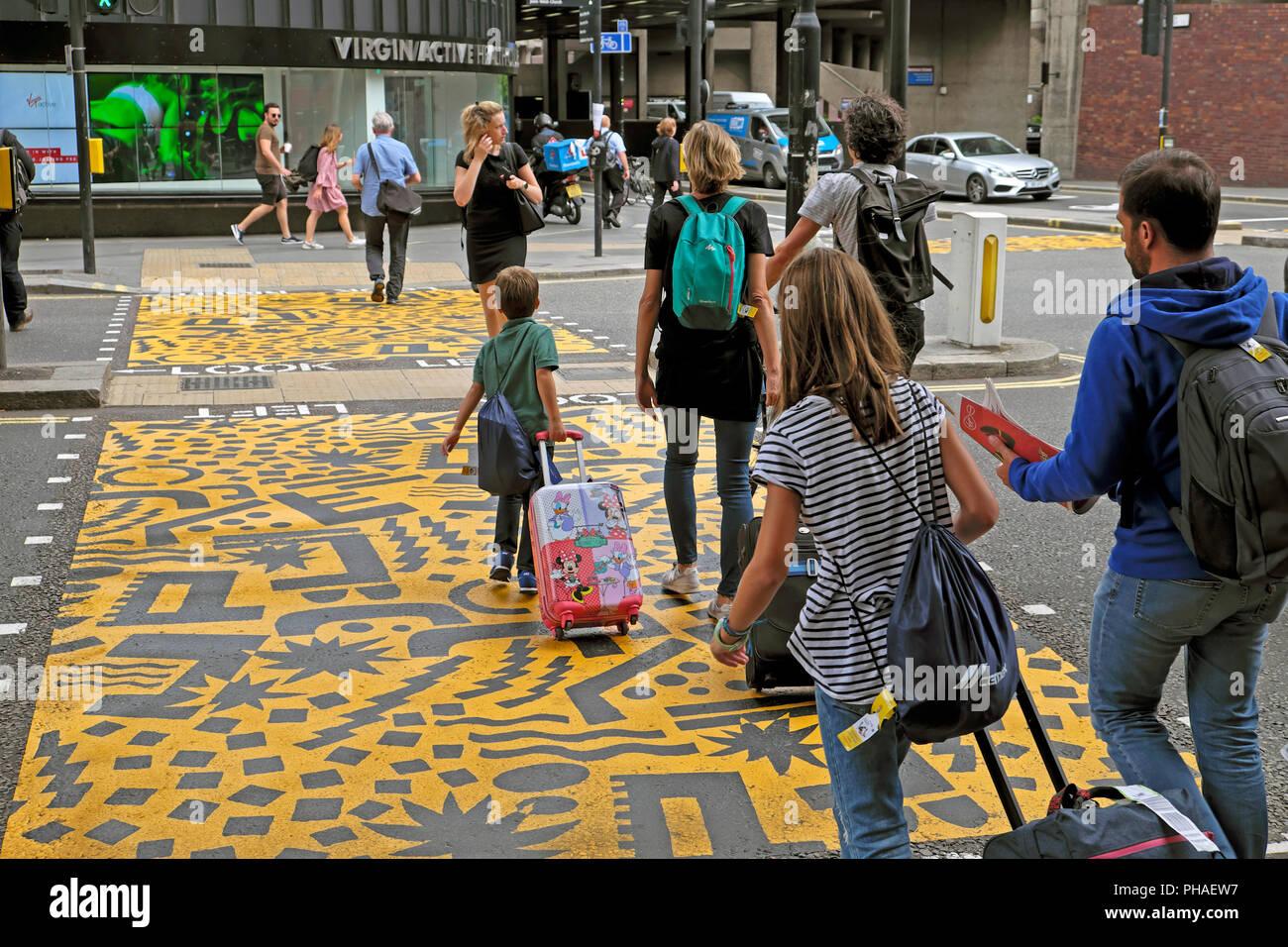 "Familie mit Gepäck auf Eley Kishimoto Kunst' farbenfrohe Kreuzungen"" Buche Street Tunnel & Barbican Station, Kulturmeile, Stadt London UK KATHY DEWITT Stockbild"
