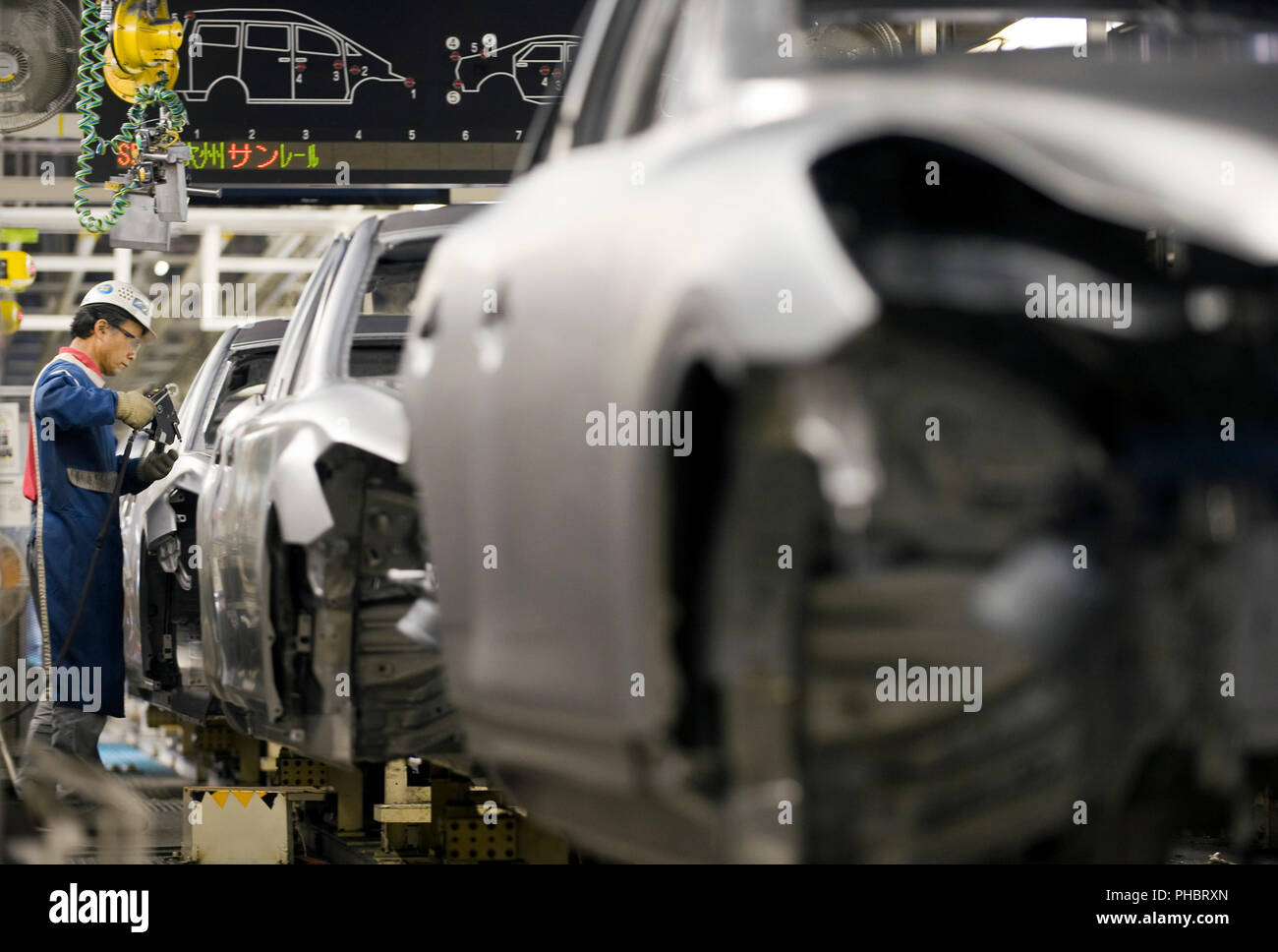 Ein Arbeitnehmer arbeitet an einem Fahrzeug bei Nissan Motor Co. s Montagewerk in Tochigi, Japan am Donnerstag, den 12. November 2009. Fotograf: Robert Gilhooly Stockbild