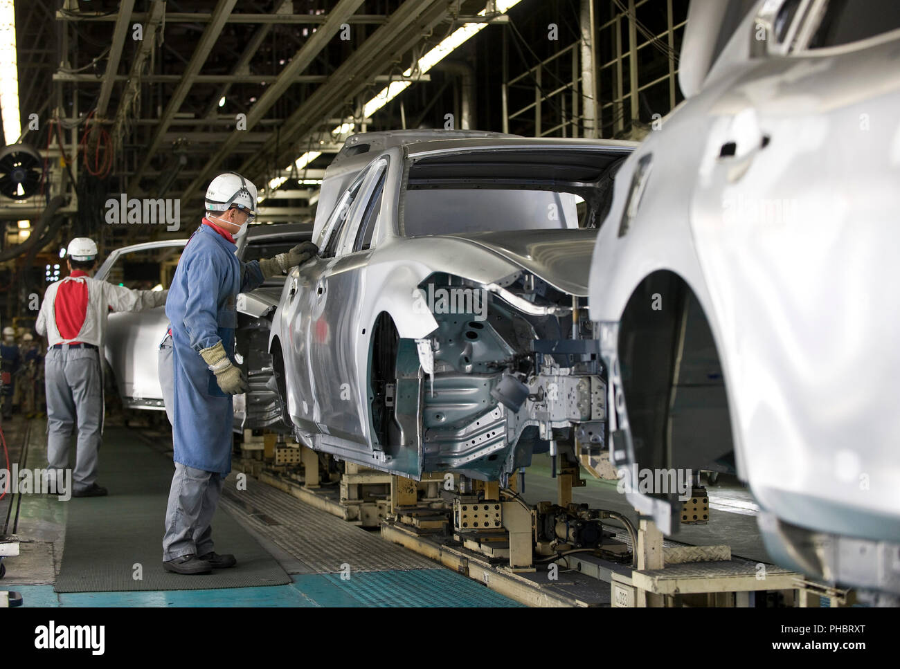 Mitarbeiter arbeiten an einem Fahrzeug bei Nissan Motor Co. s Montagewerk in Tochigi, Japan am Donnerstag, den 12. November 2009. Fotograf: Robert Gilhooly Stockbild