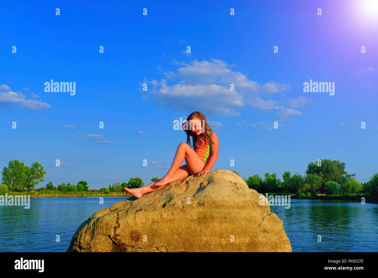 Kleines Mädchen in einem Badeanzug ist sittting auf dem Felsen und der Blick in die Ferne. Adorable Mädchen am Sonnenuntergang. Sommer und glückliche Kindheit Konzept. Kopieren Sie Raum in der strahlend blaue Himmel Stockfoto