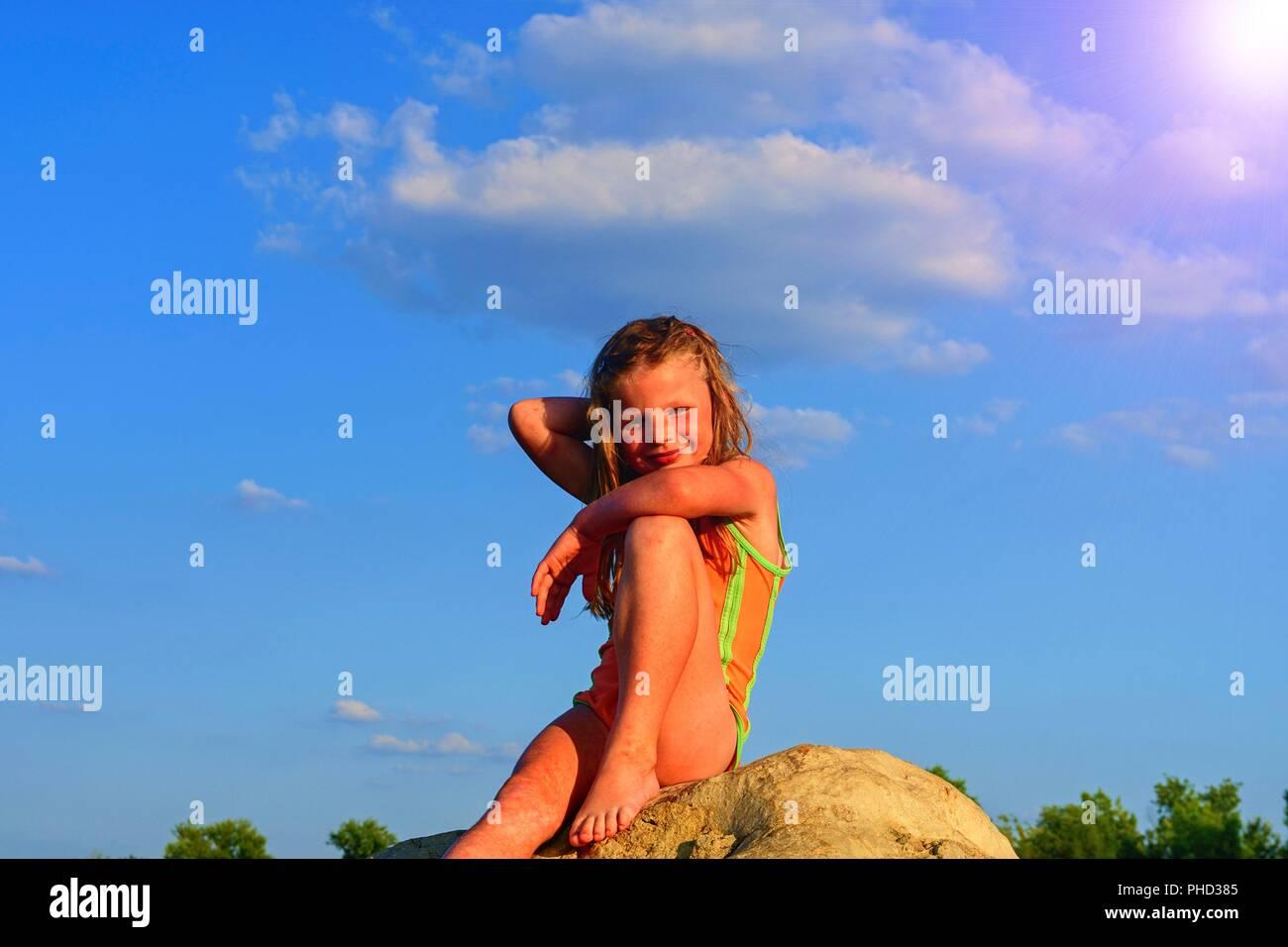 Süße kleine Mädchen im Badeanzug auf einem großen Felsen am See bei Sonnenuntergang. Sommer und glückliche Kindheit Konzept. Kopieren Sie Raum in der strahlend blaue Himmel Stockfoto