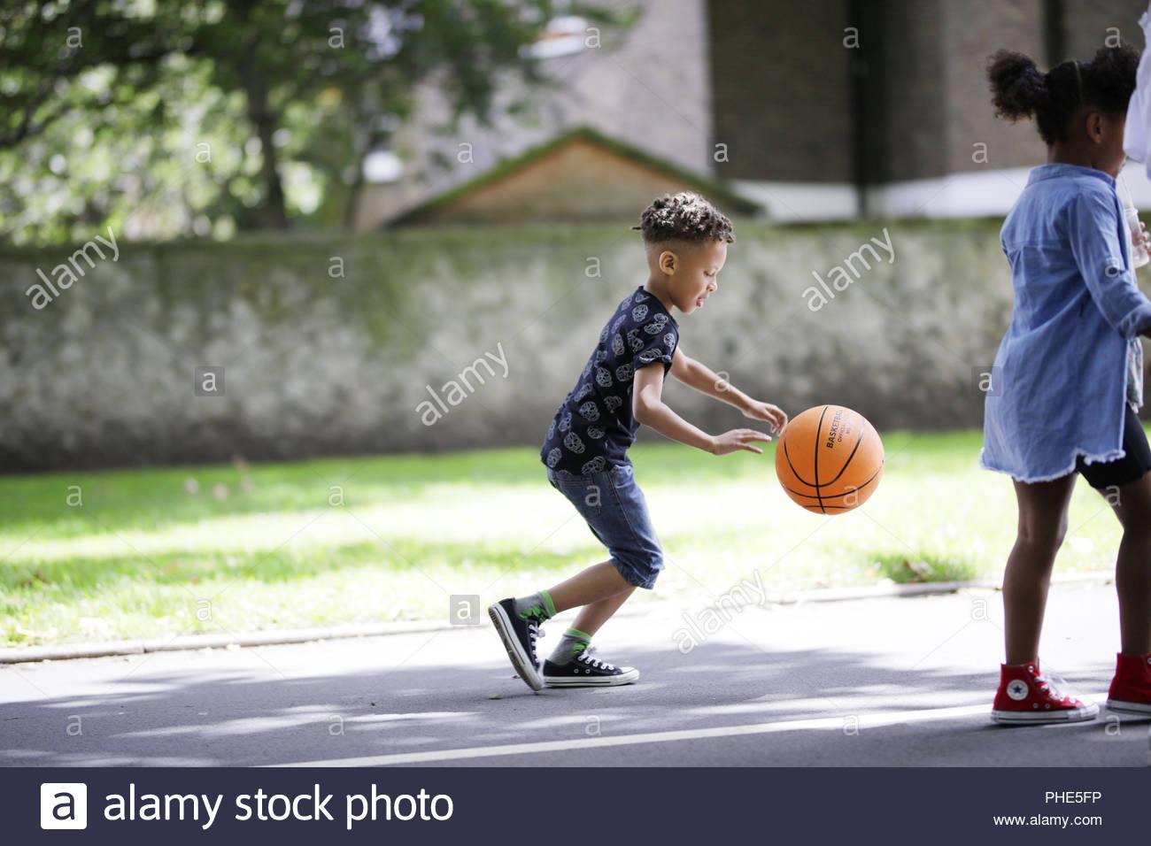 Junge spielt Basketball in Park Stockbild