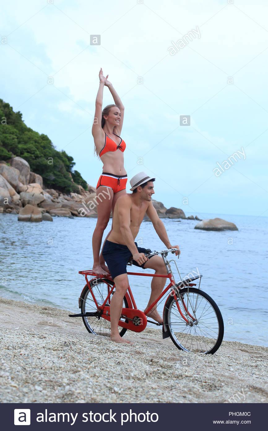 Junges Paar Radfahren am Strand Stockbild